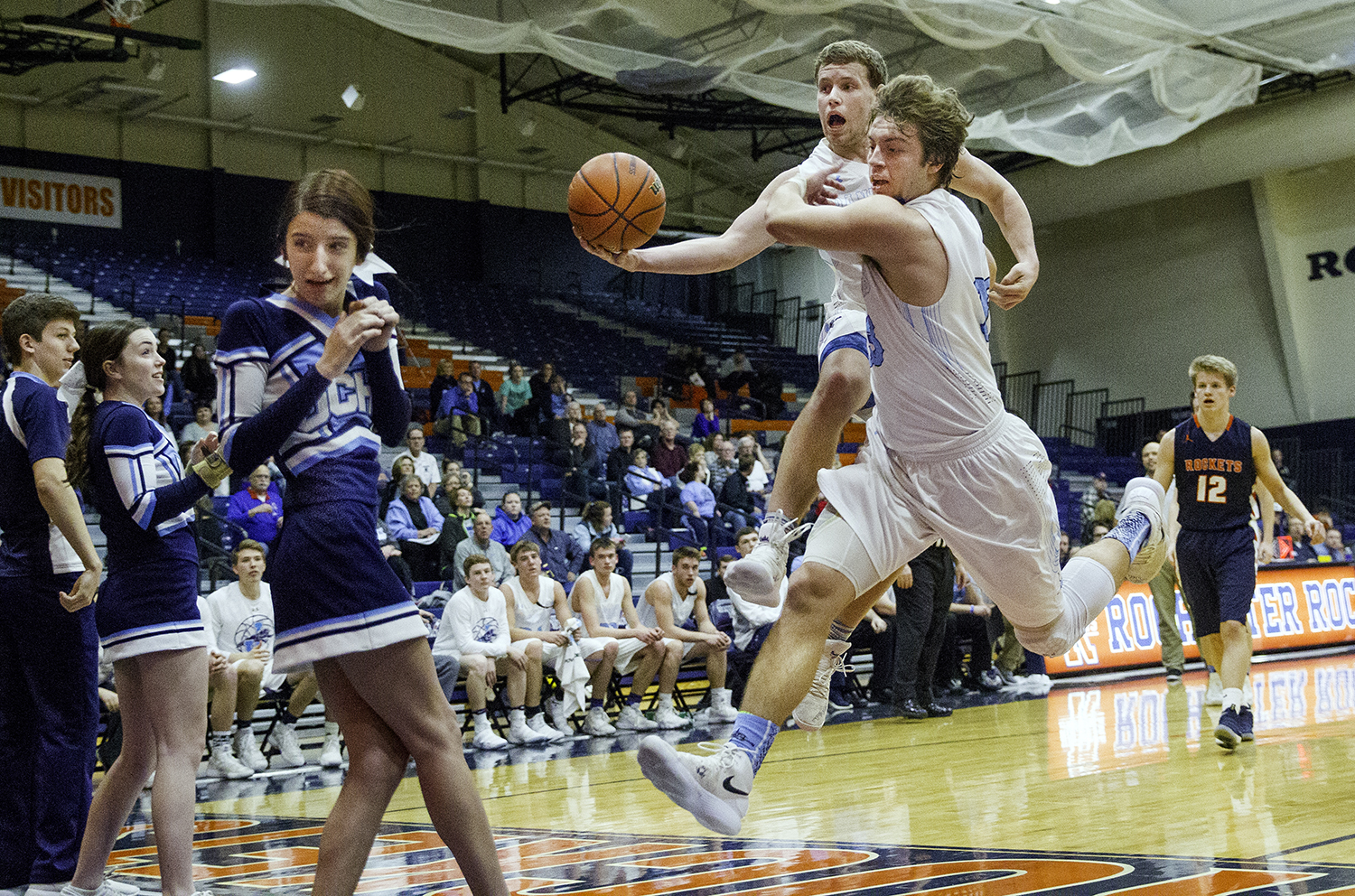 Jerseyville's Kurt Hal tries to save a loose ball as he and Jerseyville's Lucas Ross fly out of bounds near a row of cheerleaders during the Rochester Class 3A Regional Feb. 26, 2018. [Ted Schurter/The State Journal-Register]