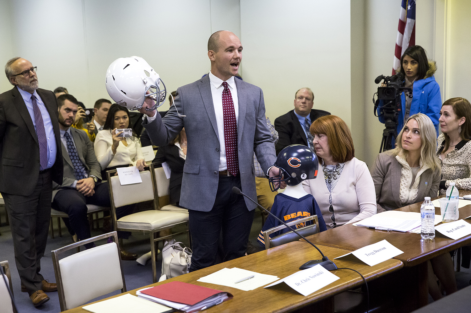 Chris Borland, a former NFL linebacker and Big Ten Defensive Player of the Year for the University of Wisconsin, testified before the Illinois House Mental Health Committee hearing on House Bill 4341, which would ban tackle football for kids under 12 years of age Thursday, March 1, 2018 at the Stratton Building in Springfield, Ill. Borland was illustrating how repetitive sub-concussive hits that begin when children play impact sports can be as dangerous as a single hit that results in a concussion. [Rich Saal/The State Journal-Register]
