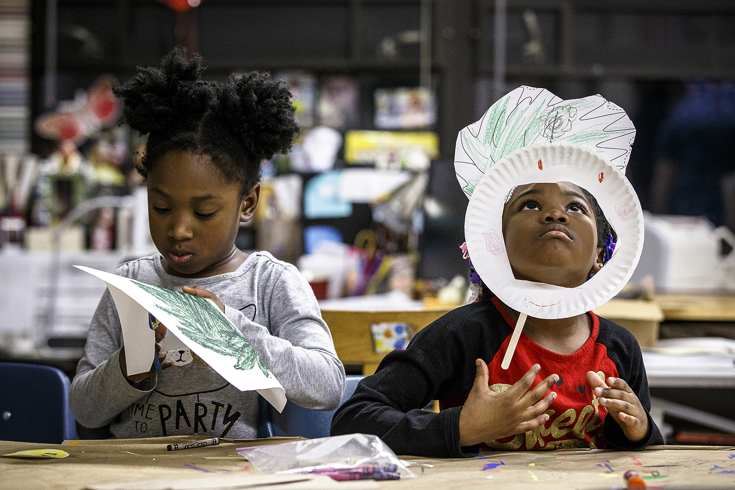 """Khaliyah Craig, right, tries out her Thing One mask from the Dr. Seuss book """"The Cat In the Hat"""" as McKenzie Woods, left, finishes up her own version as the kindergartners, and fellow students and their families, attend Literacy Night celebrating reading at Ball Charter School, Thursday, March 1, 2018, in Springfield, Ill. The event, which included the mask making, poetry out loud, guest reader and a family reader's theater, is part of the National Education Association's Read Across America program that celebrates reading on the birthday of author Dr. Seuss.  [Justin L. Fowler/The State Journal-Register]"""