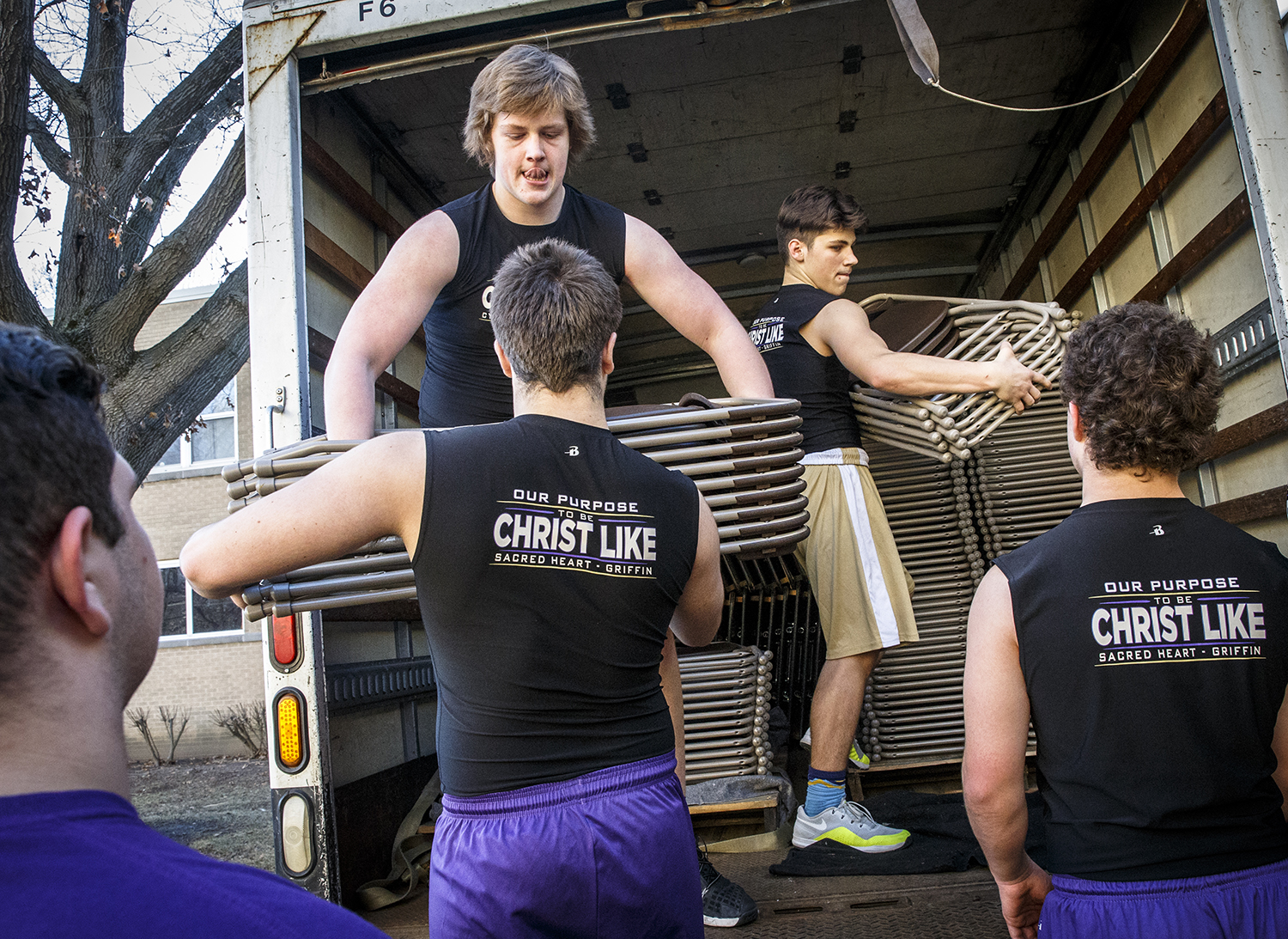 Sacred Heart-Griffin sophomore's Wes Hine, left, and Bradyn Smith, right, pass off chairs to their football teammates as they make quick work of a truckload of tables and chairs to be used in the dinning hall for the 59th year of the mostaccioli dinner at Sacred Heart-Griffin High School's West Campus, Friday, March 2, 2018, in Springfield, Ill. [Justin L. Fowler/The State Journal-Register]