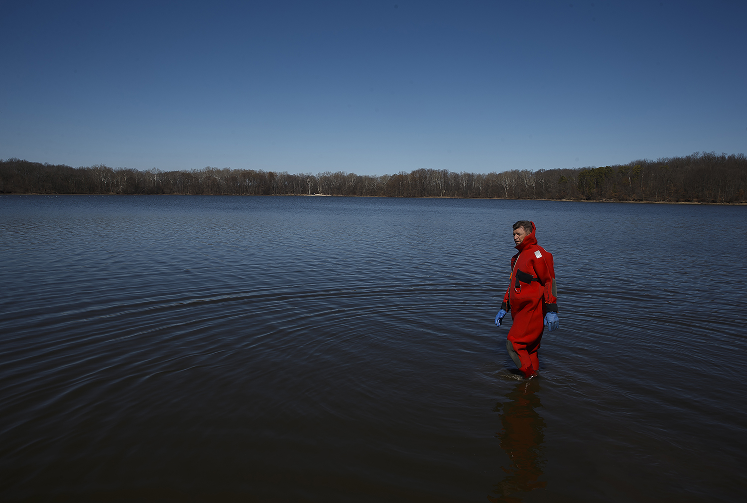 Captain Scott Weitekamp of the Springfield Fire Department looks for any large rocks or debris to remove from the plunge area during the 2018 Polar Plunge benefiting the Special Olympics Illinois on Lake Springfield at the Knights of Columbus Lake Club, Saturday, March 3, 2018, in Springfield, Ill. The low levels of Lake Springfield caused the plunge to be a bit shorter than usual as they didn't want participants to get stuck in the muck. [Justin L. Fowler/The State Journal-Register]
