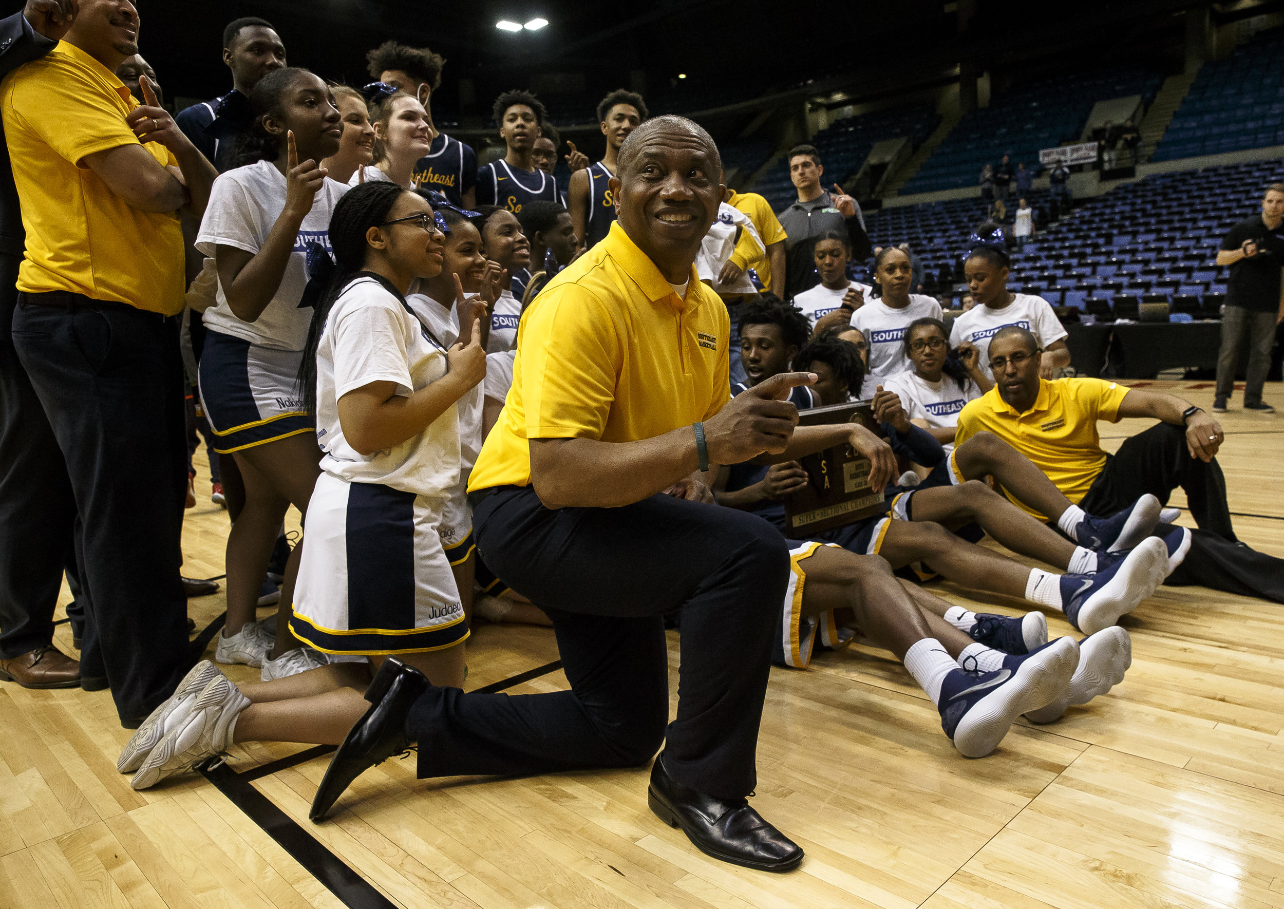 Southeast boys basketball head coach Lawrence Thomas joins his team to celebrate after the Spartans defeated Marion 56-51 in the Class 3A Springfield Supersectional at the Bank of Springfield Center, Tuesday, March 13, 2018, in Springfield, Ill. [Justin L. Fowler/The State Journal-Register]