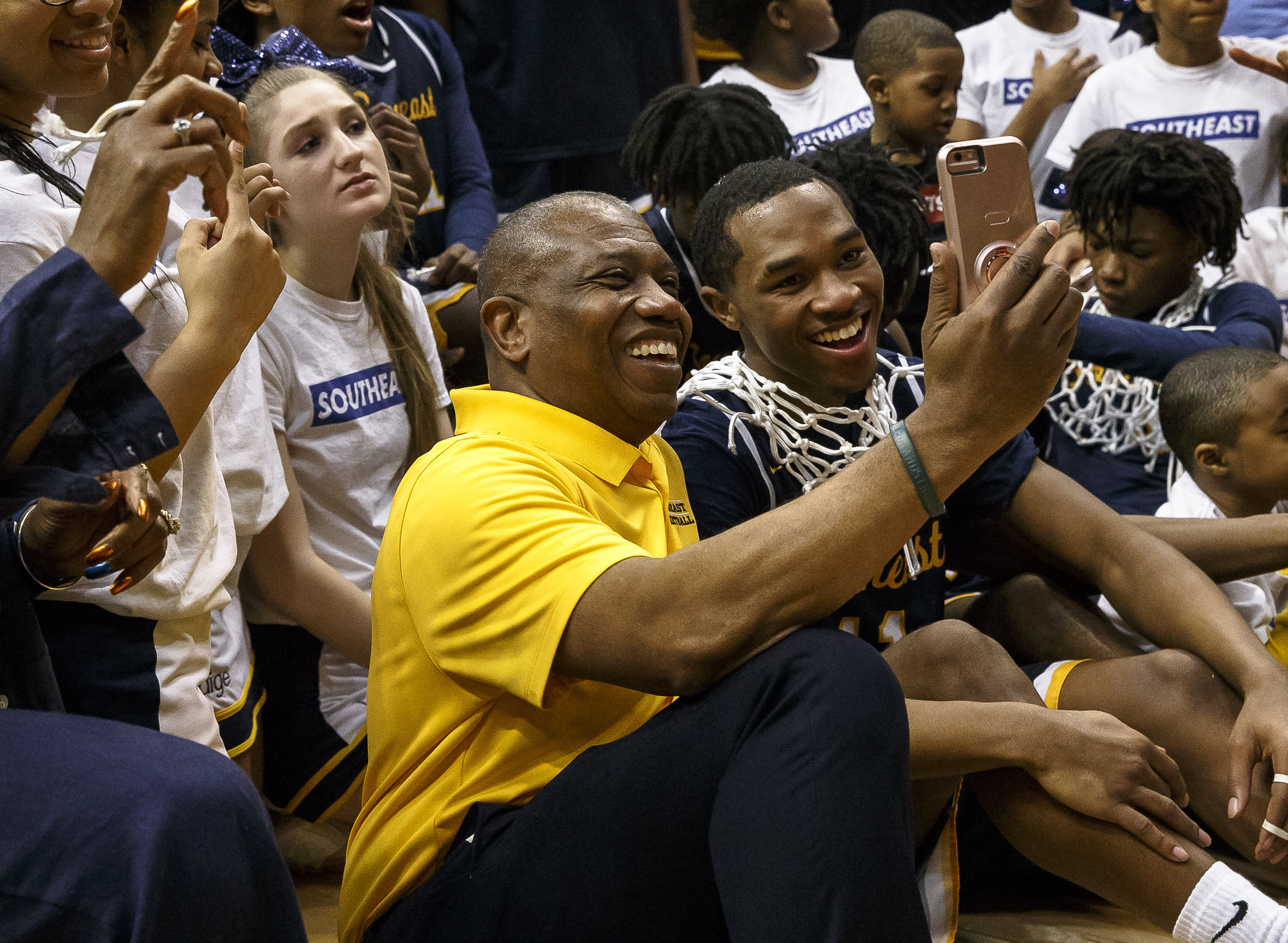 Southeast boys basketball head coach Lawrence Thomas video chats with his son and former Spartan as they celebrate their 56-51 victory over Marion in the Class 3A Springfield Supersectional at the Bank of Springfield Center, Tuesday, March 13, 2018, in Springfield, Ill. [Justin L. Fowler/The State Journal-Register]