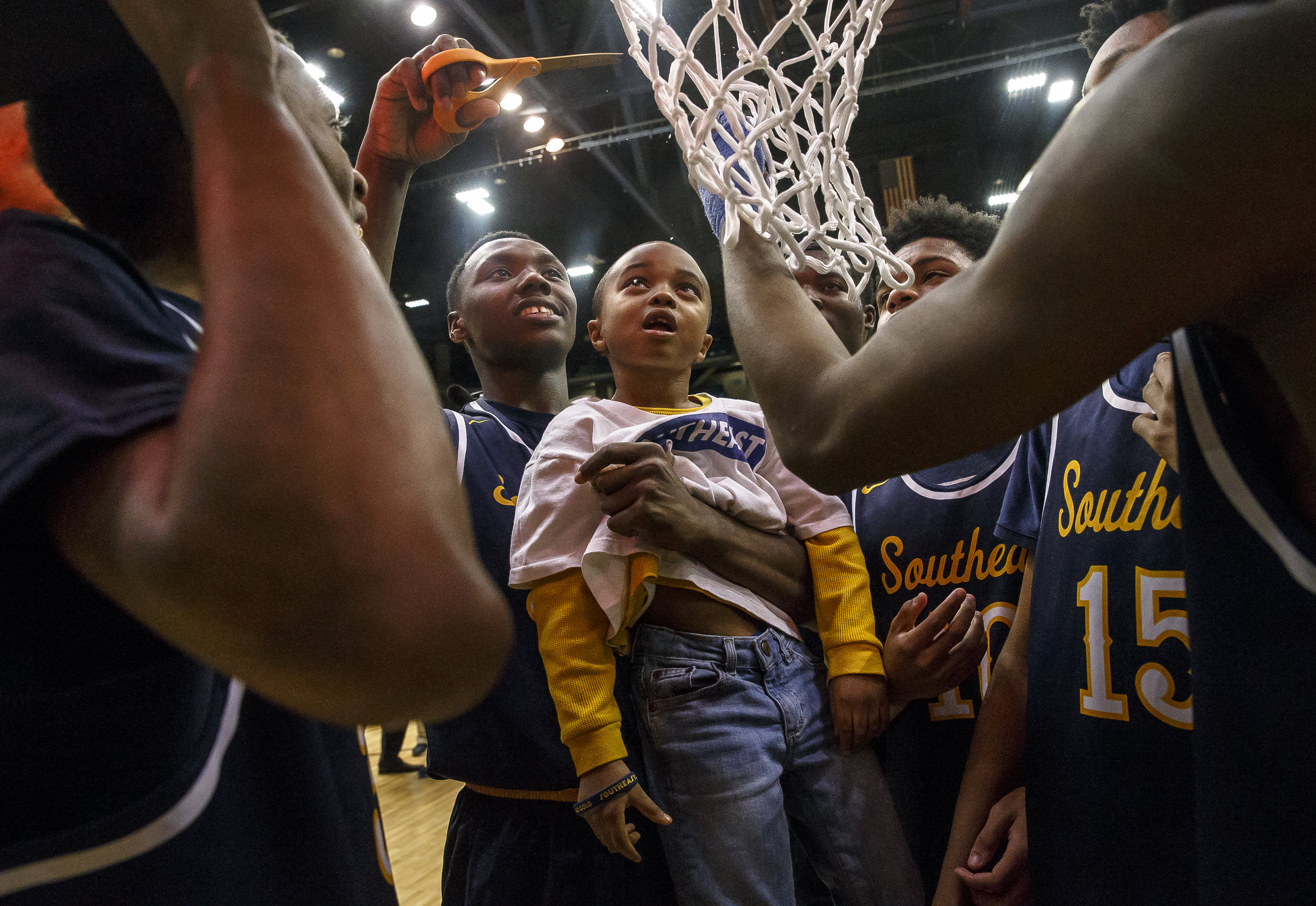 Lamar Coleman, 6, gets his piece of the net with a little help from Southeast's Devin Blue-Robinson (30) as they celebrate their 56-51 victory over Marion in the second half during the Class 3A Springfield Supersectional at the Bank of Springfield Center, Tuesday, March 13, 2018, in Springfield, Ill. [Justin L. Fowler/The State Journal-Register]