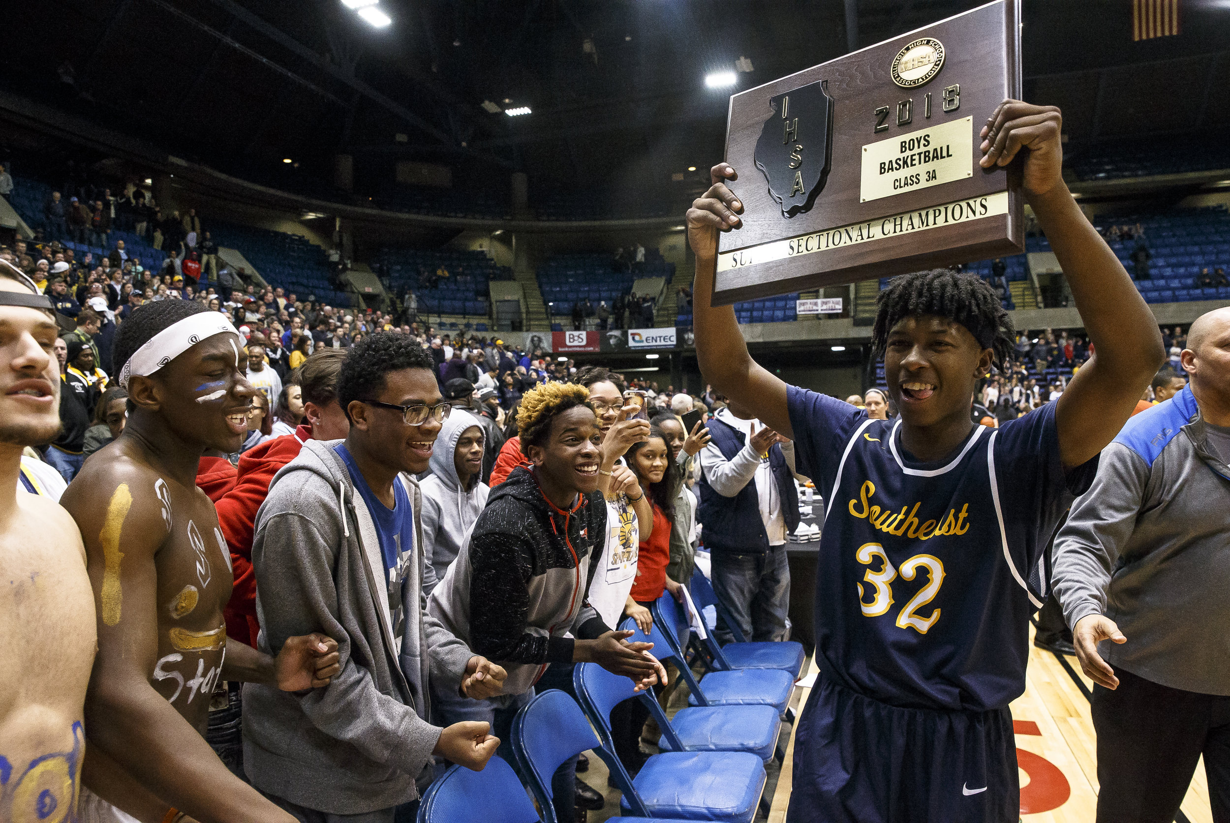 Southeast's Stepheon Sims (32) shares the championship plaque with the Southeast fans after the Spartans defeated Marion 56-51 in the Class 3A Springfield Supersectional at the Bank of Springfield Center, Tuesday, March 13, 2018, in Springfield, Ill. [Justin L. Fowler/The State Journal-Register]