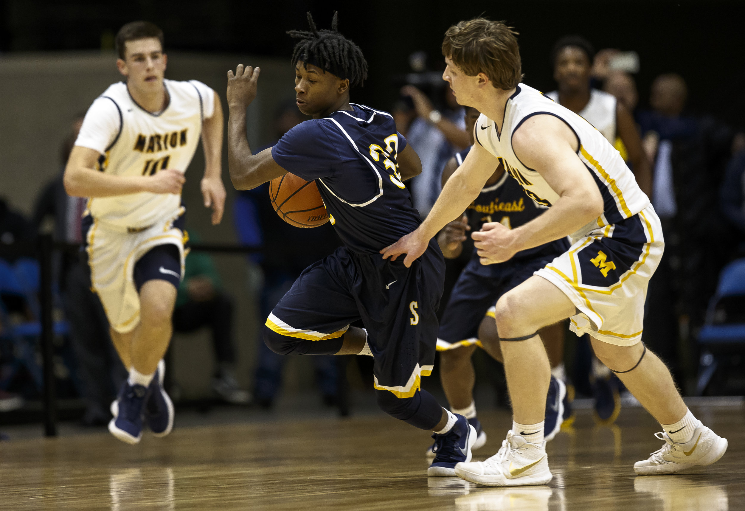 Southeast's Stepheon Sims (32) drives the ball past Marion's Justin Saddoris (13) in the first half during the Class 3A Springfield Supersectional at the Bank of Springfield Center, Tuesday, March 13, 2018, in Springfield, Ill. [Justin L. Fowler/The State Journal-Register]