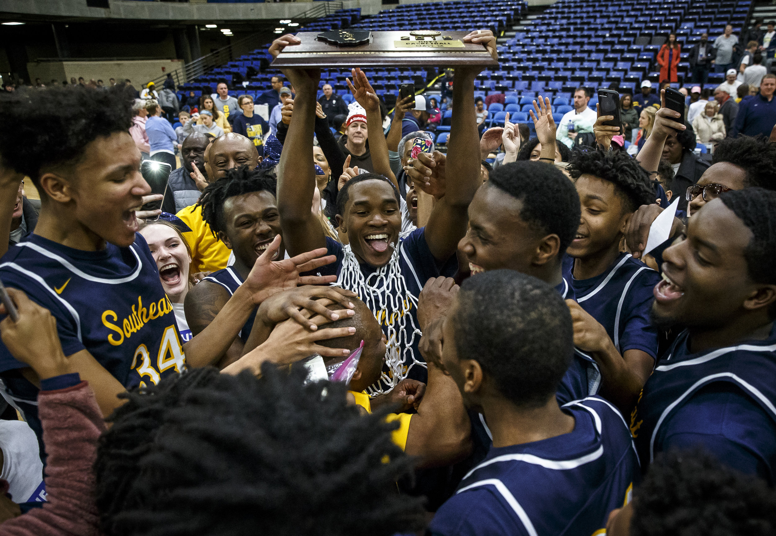 Southeast's Kobe Medley (11) and the Spartans surround Southeast boys basketball head coach Lawrence Thomas  as they celebrate their 56-51 victory over Marion in the Class 3A Springfield Supersectional at the Bank of Springfield Center, Tuesday, March 13, 2018, in Springfield, Ill. [Justin L. Fowler/The State Journal-Register]