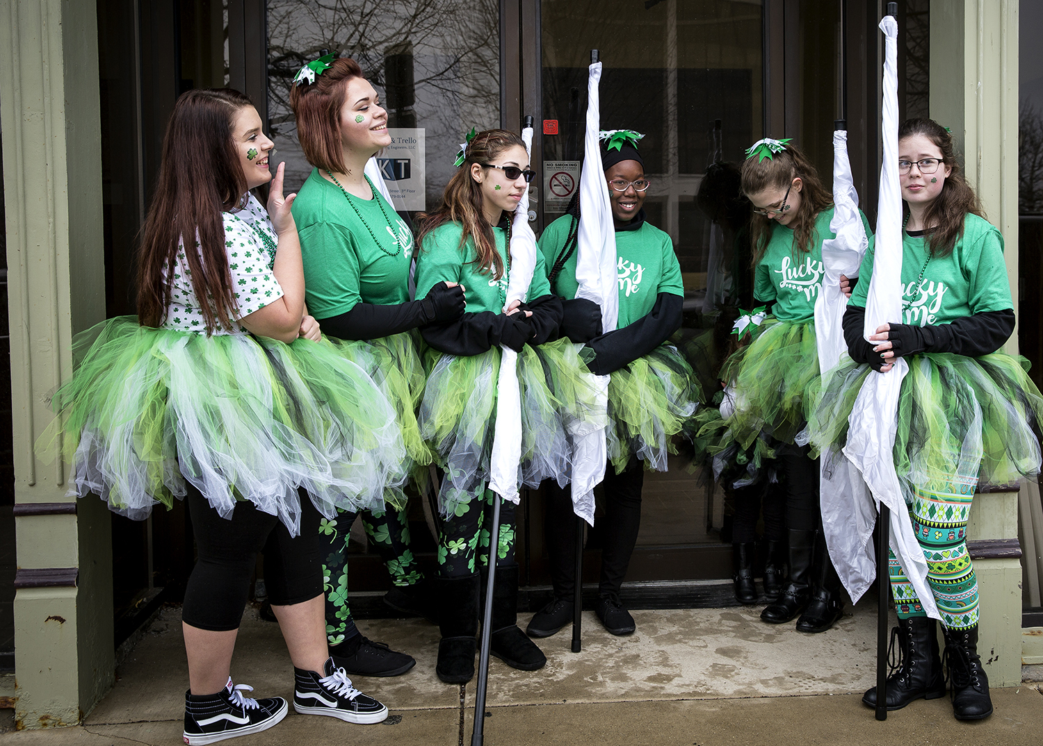 Members of the Lanphier High School marching band flag team huddle in the entrance to the Springfield Convention and Visitor's Bureau before the start of the St. Patrick's Day Parade Saturday, March 17, 2018  in Springfield, Ill. [Rich Saal/The State Journal-Register]