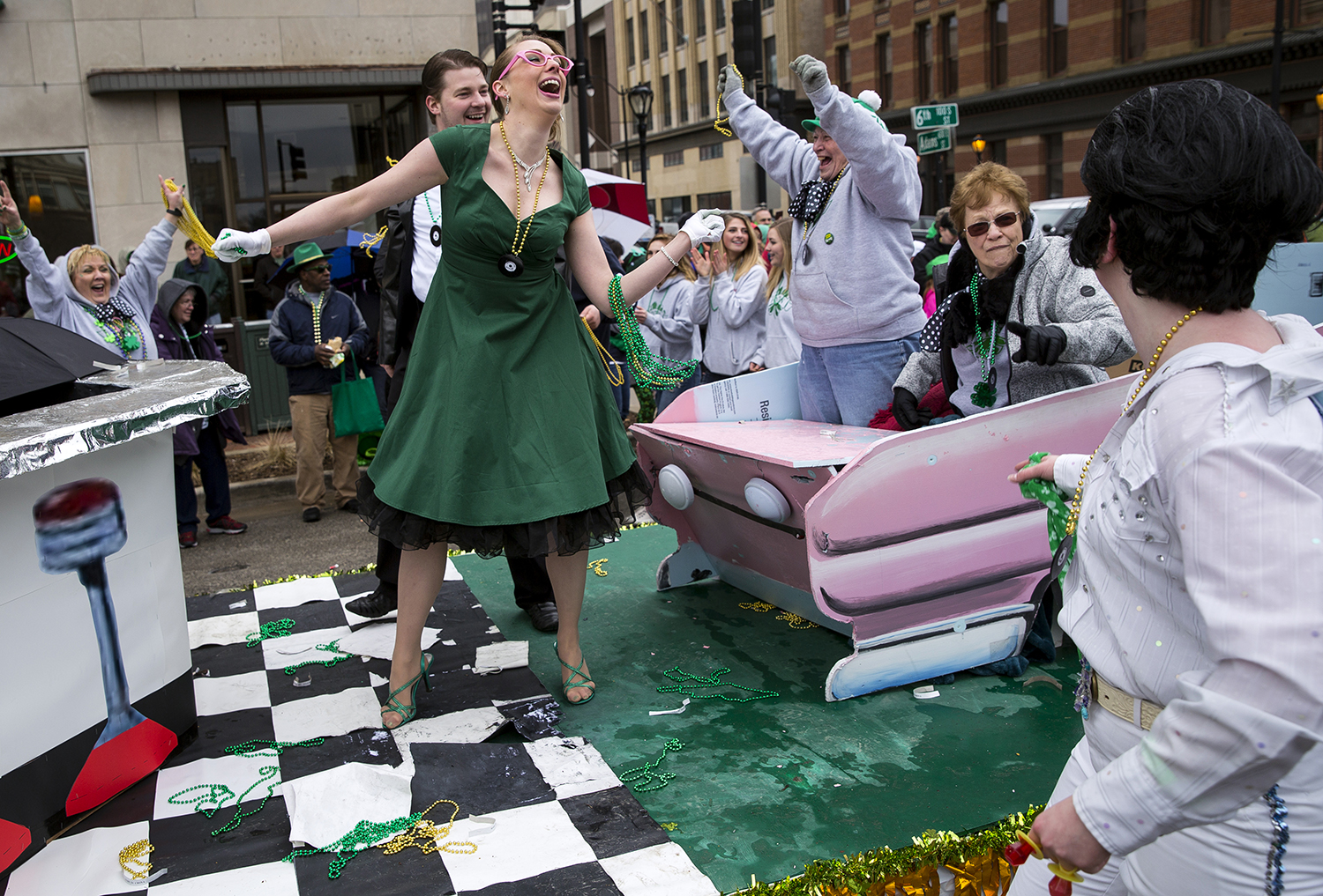Kerri Ryan, center, and other members of the extended Ryan family celebrate when they pass the review stand and hear that their float, the Shamrock n' Roll Ryans, received first place during the St. Patrick's Day Parade Saturday, March 17, 2018  in Springfield, Ill. [Rich Saal/The State Journal-Register]