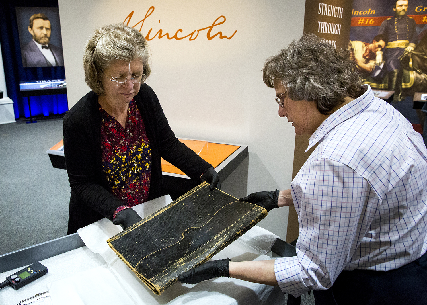 Carla Smith, left, registrar for the Abraham Lincoln Presidential Library and Museum, and Bonnie Parr, historical documents conservator at the presidential library, move a leather folio used by Abraham Lincoln to an exhibit case for a special exhibit that coincides with the Illinois bicentennial Wednesday, March 21, 2018 at the presidential museum. ÒFrom Illinois to the White House: Lincoln, Grant, Reagan, Obama,Ó honors the four U.S. presidents with close ties to the state. It opens Friday to the public. [Rich Saal/The State Journal-Register]