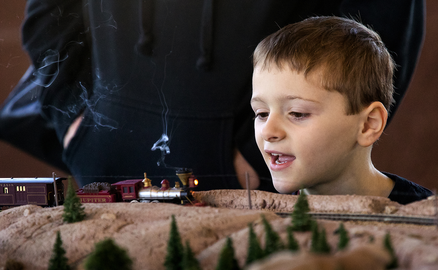 """Six-year-old Beckett Bishop watches as a model of """"The Jupiter,"""" one of two locomotives that met at Promontory Summit during the ceremony that joined the transcontinental railroad, blows  artificial smoke from its stack as it rounds a bend at the Springfield Railroad Society Train Fair at the Orr Building on the Illinois State Fairgrounds Sunday, March 25, 2018. The one-day show featured operating rail layouts as well buying selling and trading of model railroad equipment. [Ted Schurter/The State Journal-Register]"""