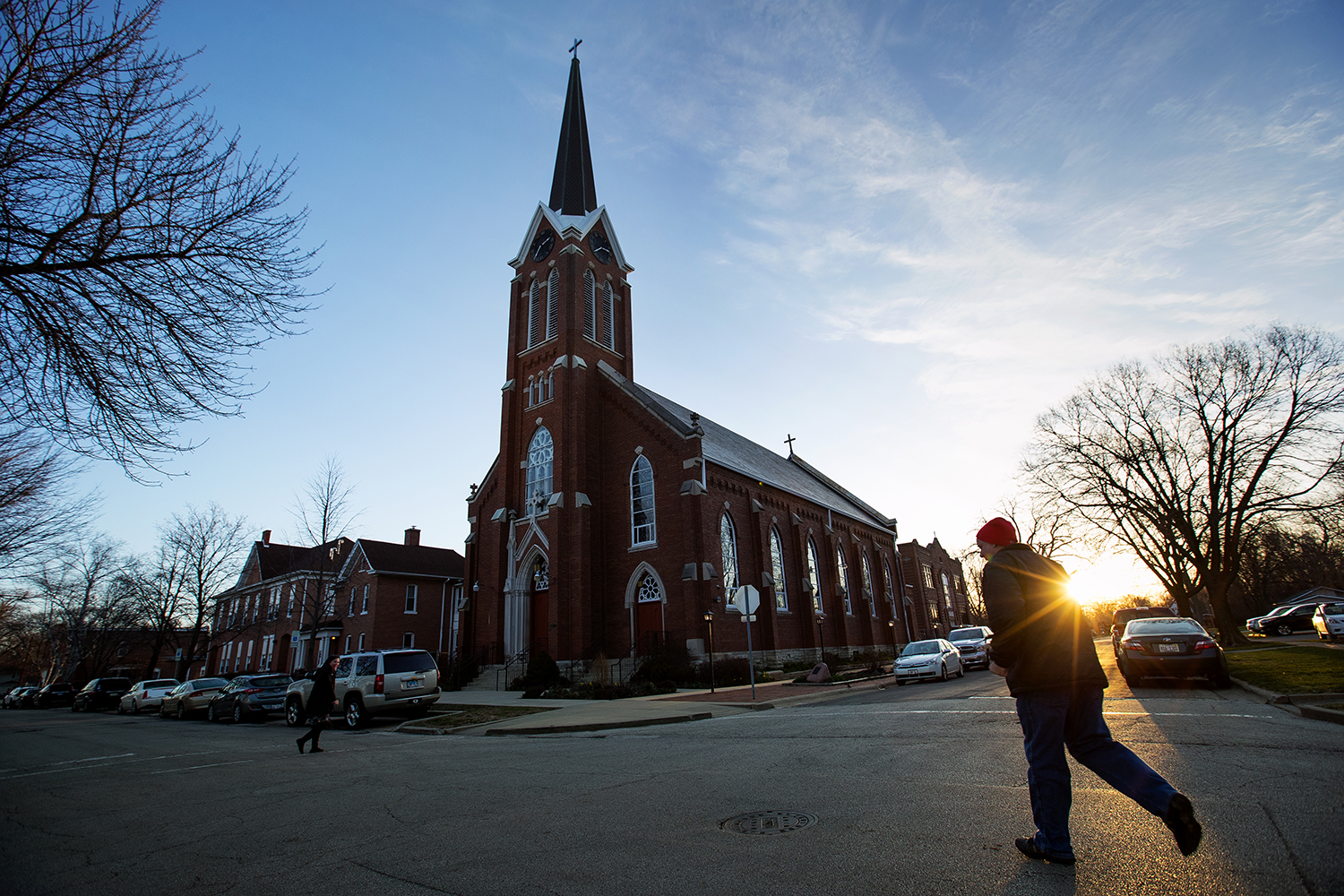 The sun rises over the horizon as a young man hurries across East Lawrence Avenue to get to Sacred Heart Church for the 7 a.m. Mass on Easter Sunday, April 1, 2018. [Ted Schurter/The State Journal-Register]
