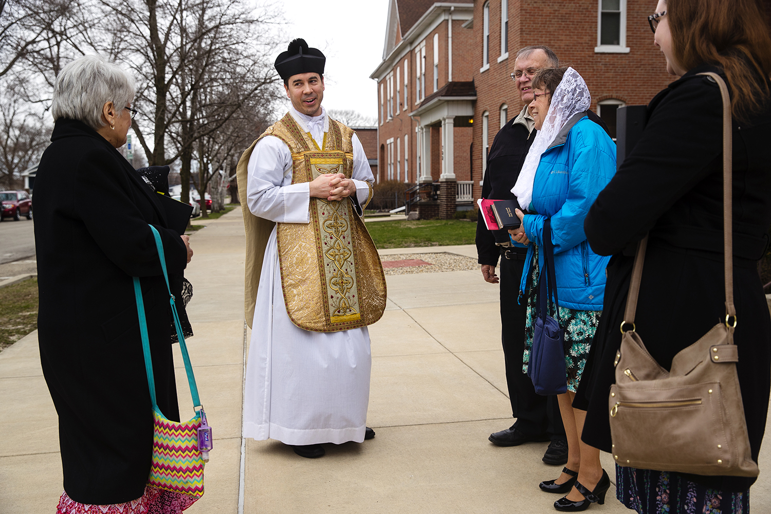 Father Trenton Rauck greets parishioners following the Latin Mass on Easter Sunday at Sacred Heart Church in Springfield, Ill., April 1, 2018. [Ted Schurter/The State Journal-Register]