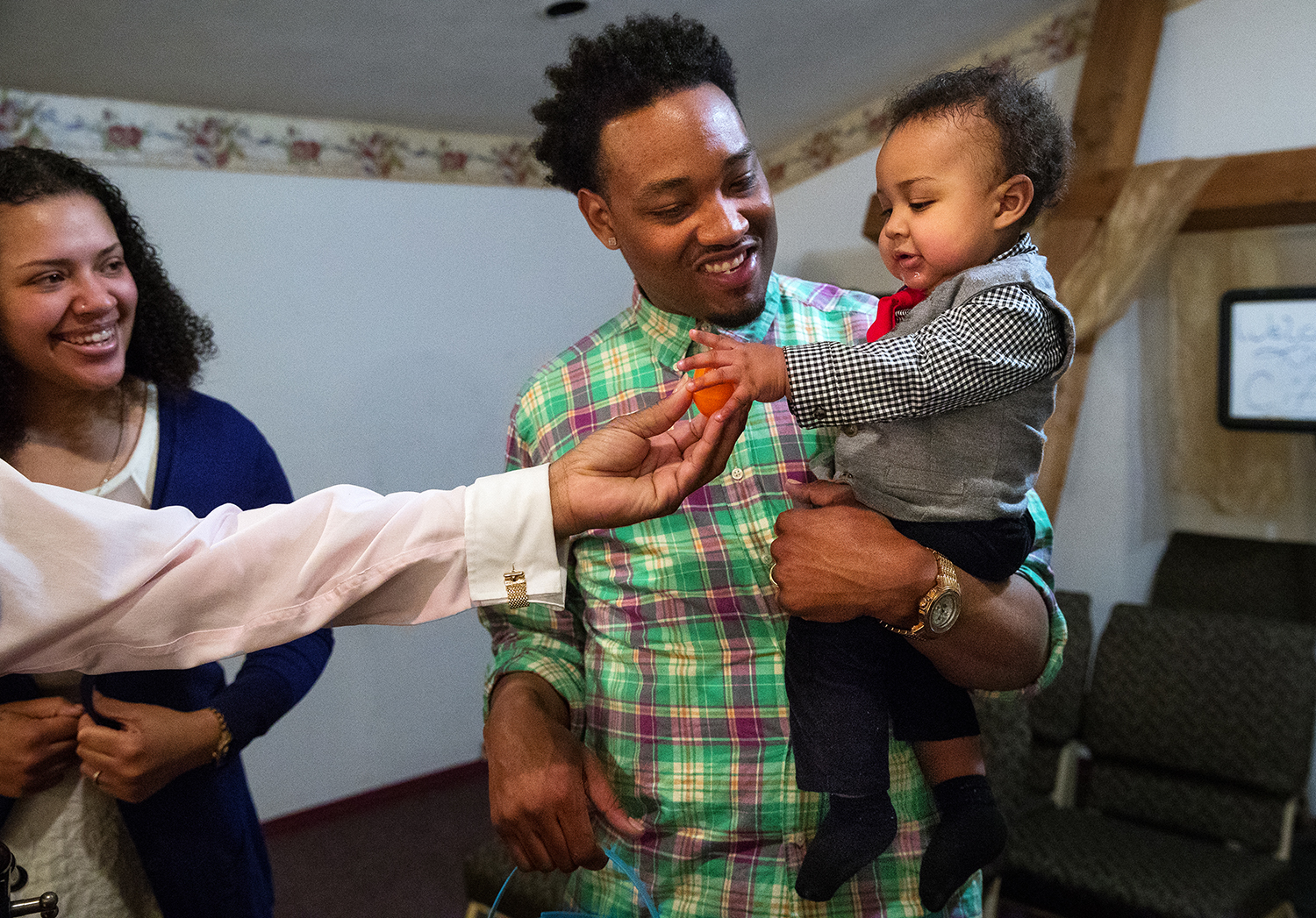 Todd Gordon Jr. holds his infant son Todd as he takes an Easter egg from his grandfather Bishop Todd Gordon Sr. after an Easter egg hunt at City of Miracles International church in Springfield on Easter Sunday, April 1, 2018. [Ted Schurter/The State Journal-Register]