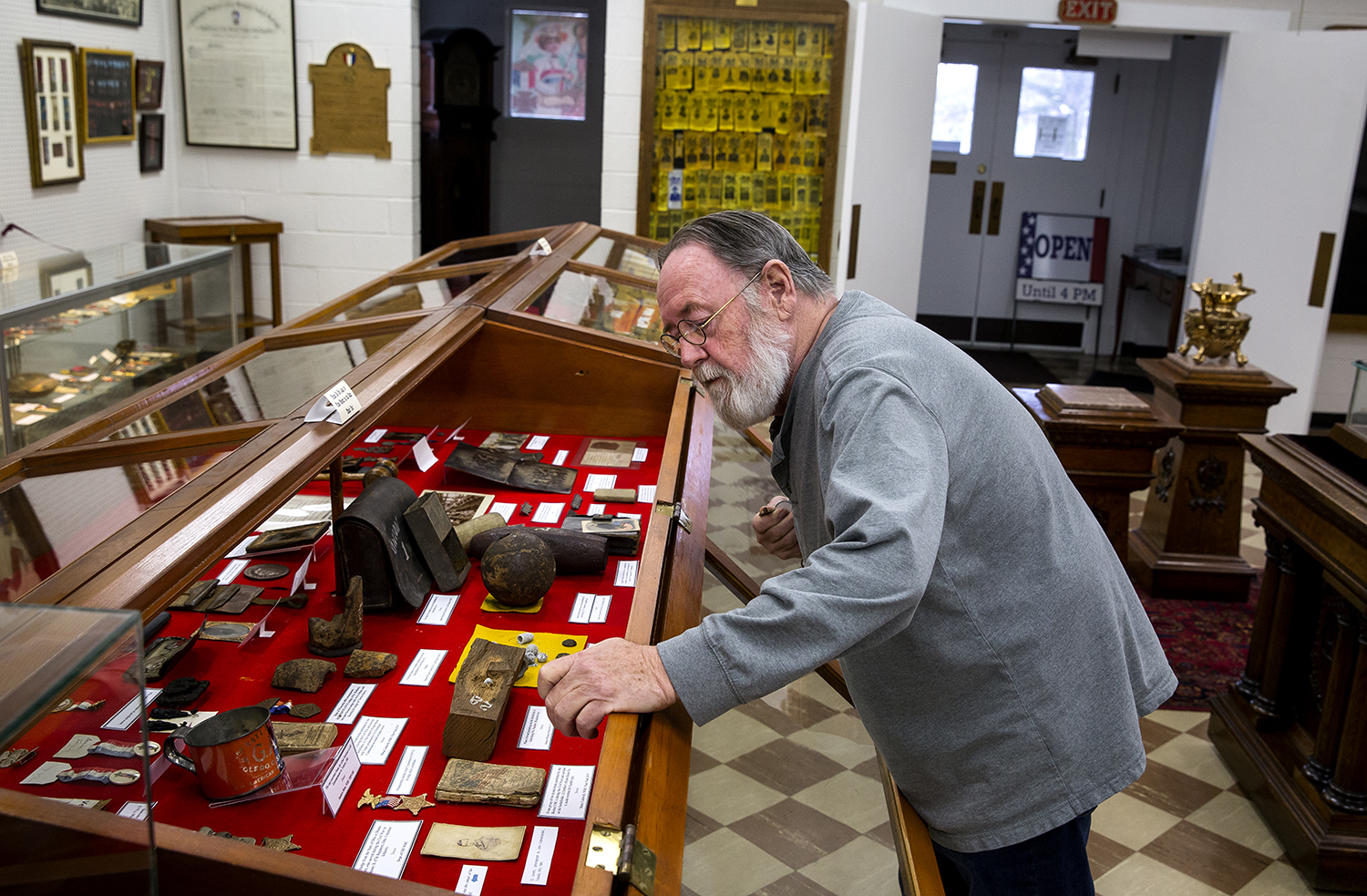 Chuck Hill, curator of the Grand Army of the Republic Memorial Museum, places notes in a case Tuesday, April 3, 2018 at the museum in Springfield, Ill. [Rich Saal/The State Journal-Register]