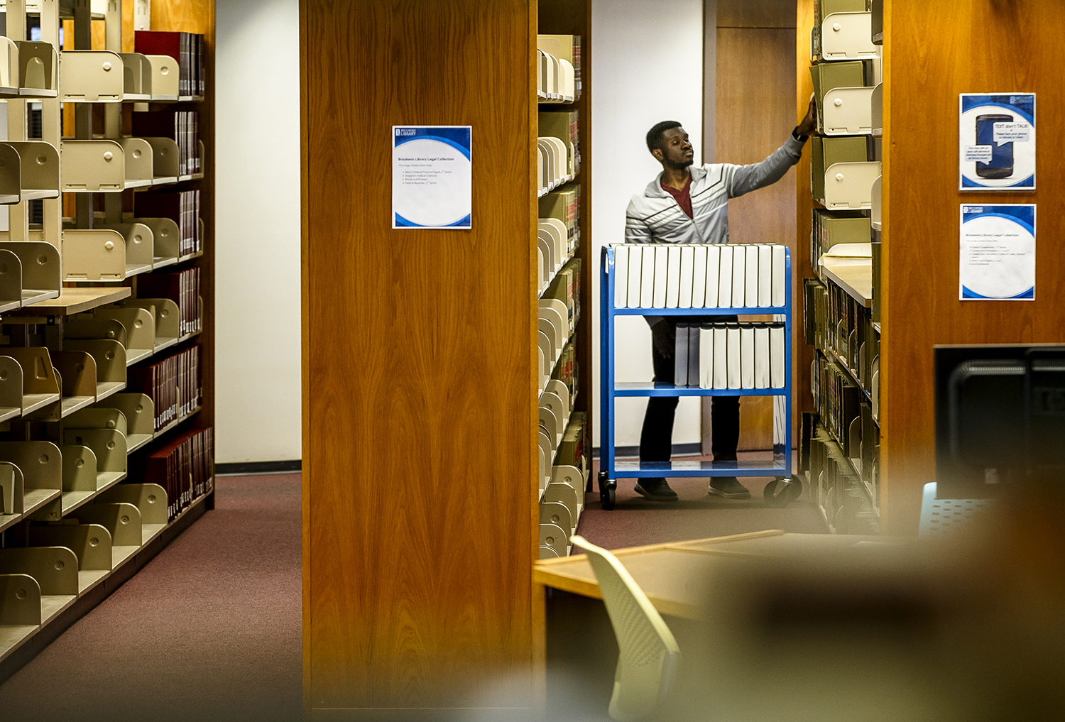 Daniel Asare, a student assistant at the University of Illinois Springfield's Brookens Library, moves volumes of Federal Supplements from one section of the library to another floor, Thursday, April 5, 2018, in Springfield, Ill. University officials are advocating for nearly $600 million in capital spending for the U of I system, specifically the need for library renovations on all three campuses, including a more than $58 million facelift for Brookens Library at UIS. [Justin L. Fowler/The State Journal-Register]