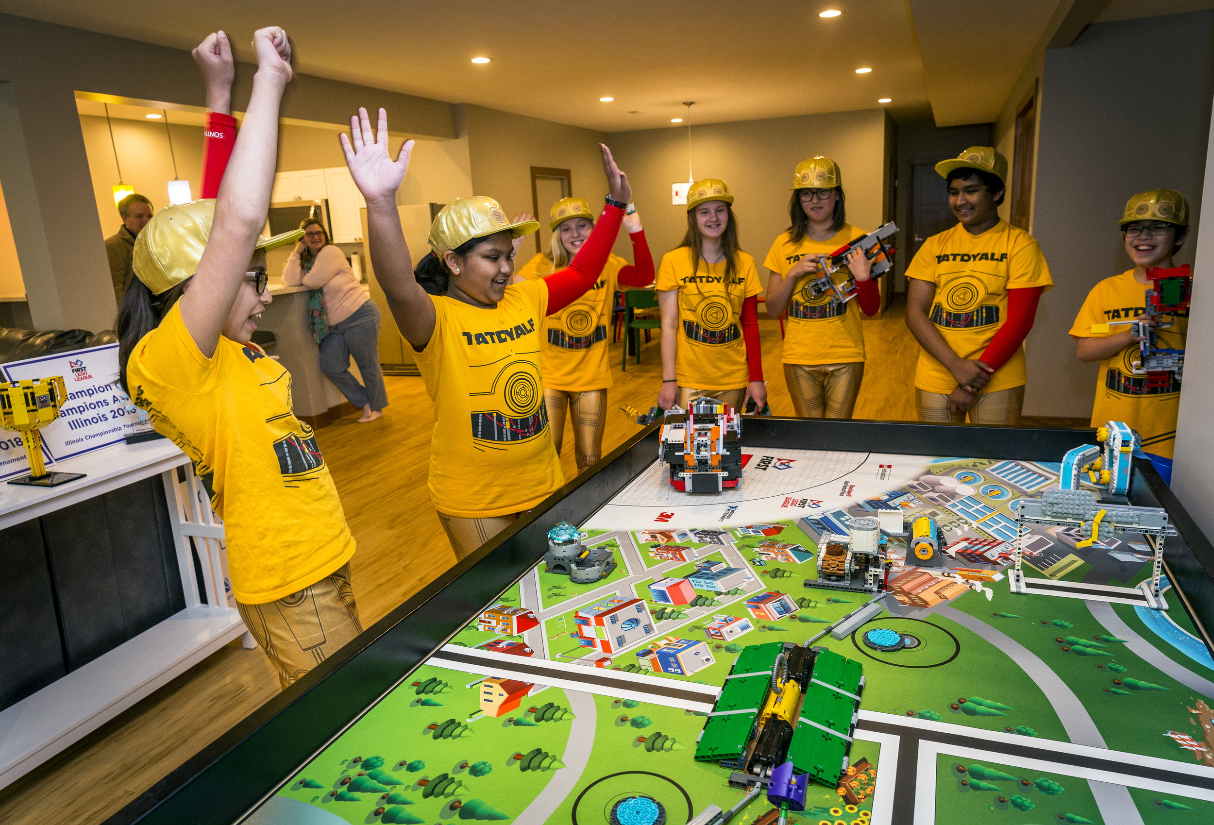 "Isha Ramkumar, 10, left, celebrates with her teammates on the These Are The Droids You Are Looking For (TATDYALF) team as their autonomous robot named ""Bellatrix"" performs a successful mission on a FIRST LEGO League Robotics Competition board in the basement of team member Macy Sumner's home, Friday, April 13, 2018, in Springfield, Ill. These Are The Droids You Are Looking For (TATDYALF) is a team of students from Iles Elementary, Iles Middle School, and Franklin Middle School in Springfield, and Williamsville Junior High School that will compete against more than 100 champion teams from around the world at the FIRST LEGO League World Festival in Detroit, Michigan from April 25–28. [Justin L. Fowler/The State Journal-Register]"