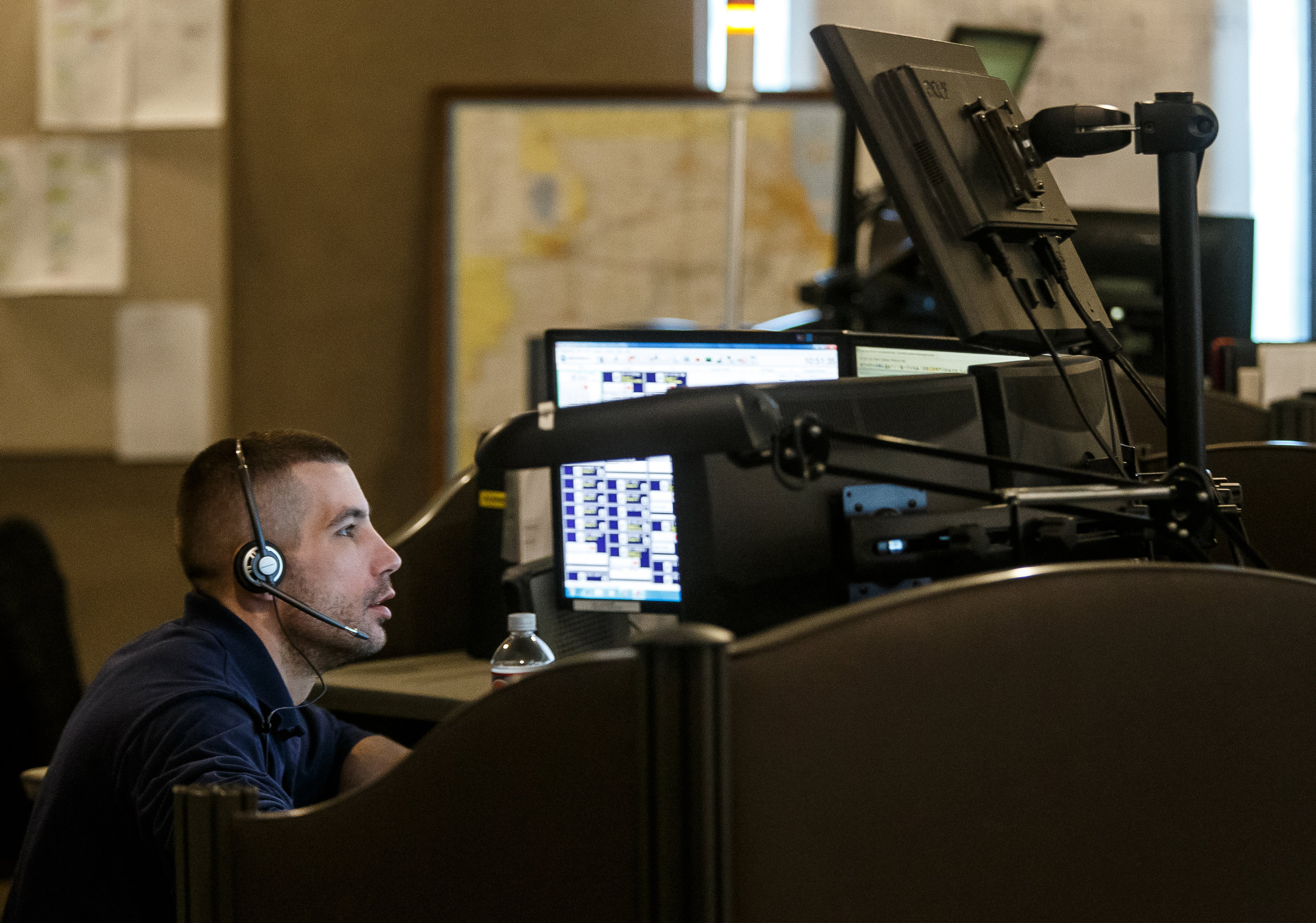Dispatcher Tyler Smith manages an array of six computer screens as he works a shift taking calls and dispatching officers at the Sangamon County 911 Center, Monday, April 16, 2018, in Springfield, Ill. [Justin L. Fowler/The State Journal-Register]