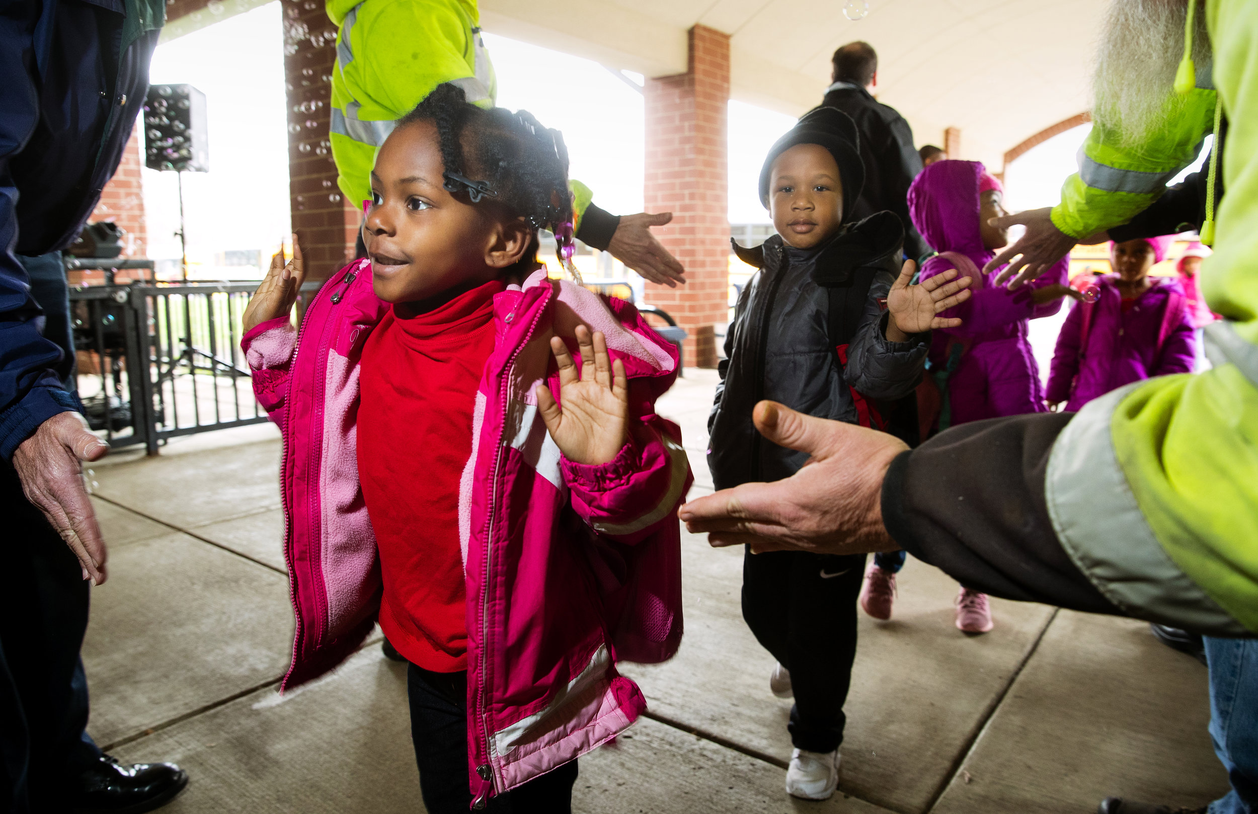 Kalise Shaw, left, and Lasshone Alexander greet Springfield city workers on their way into the Early Learning Center Monday, April 16, 2018. Employees from the mayor's office, fire, police and public works departments were all on hand to welcome the students and kick-off for Week of the Young Child, an annual event celebrating early learning, young children, their teachers & families. [Ted Schurter/The State Journal-Register]