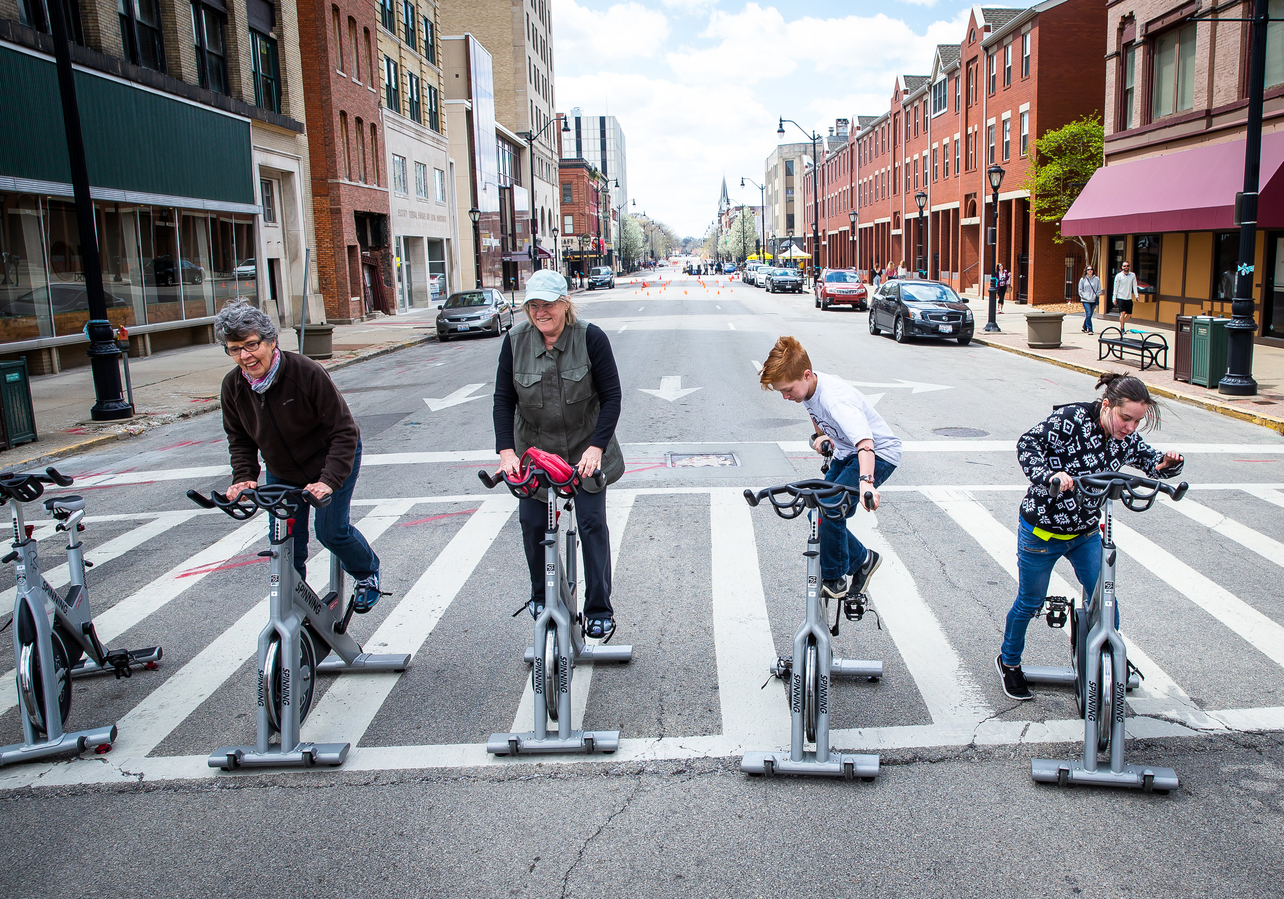"""Mary Thoele, left, Marilyn Cisco, Chandler Marquardt, 13, and Amy Thomas, 16, right, try out spin bikes during a demonstration of the YMCA spin class in the middle of a closed down Monroe Street during the Downtown Open Streets event, Saturday, April 28, 2018, in Springfield, Ill. Downtown Open Streets was an event put on by Downtown Springfield, Inc. and sponsored by Memorial Health System, and created a """"paved park"""" by temporarily closing certain downtown streets and holding demonstrations promoting recreation and healthier living. [Justin L. Fowler/The State Journal-Register]"""