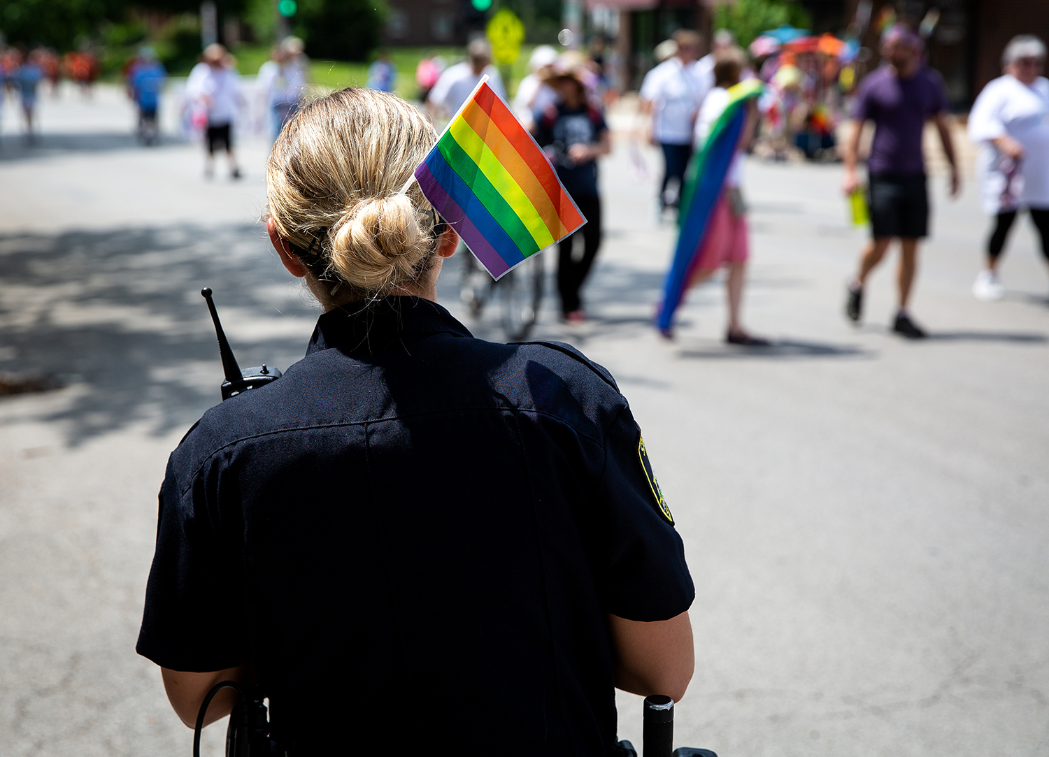 Springfield Police Officer Krystal Holdman sports a rainbow flag in her hair while conducting traffic control along Fifth Street during Springfield's PrideFest parade Saturday, May 19, 2018 in Springfield, Ill. [Rich Saal/The State Journal-Register]