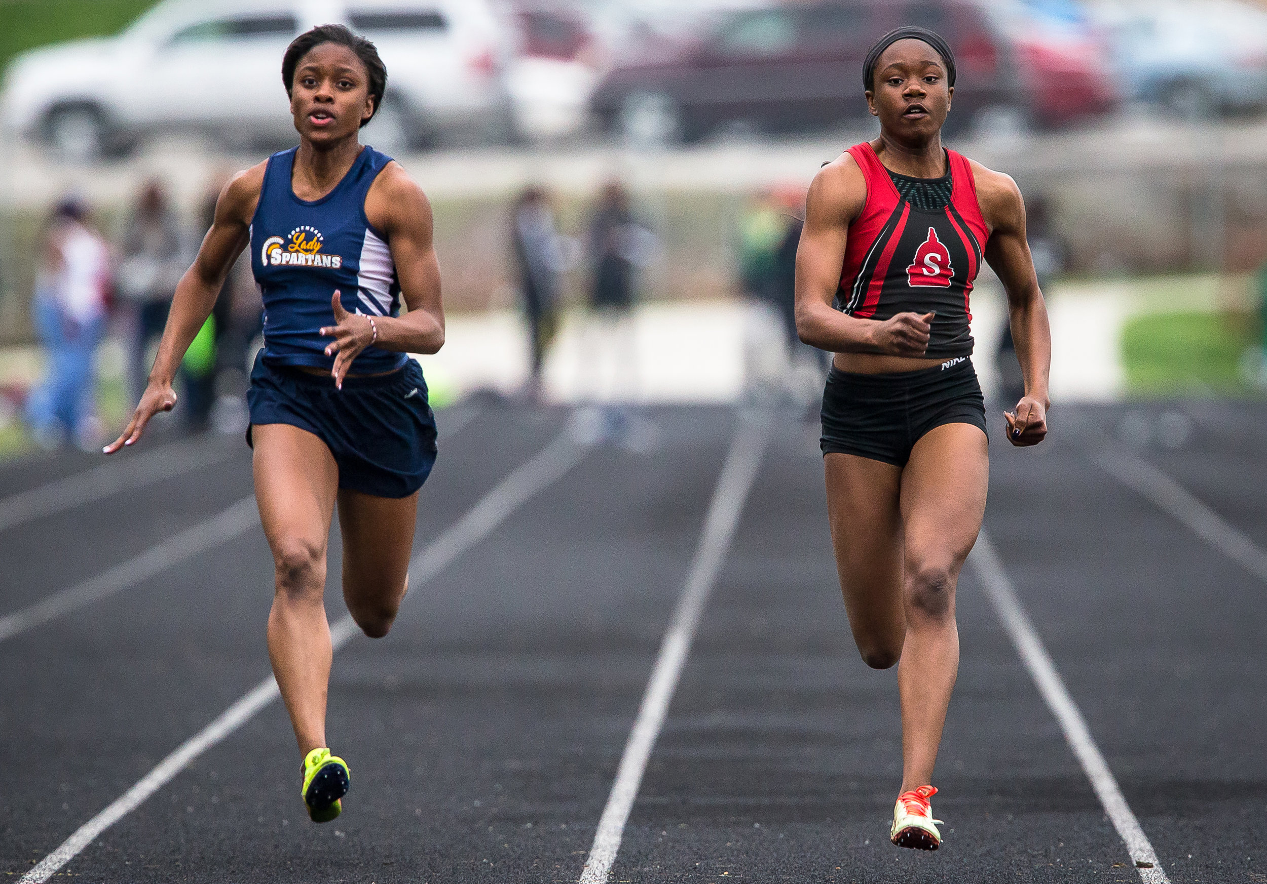 Springfield's Ozzy Erewele, right, wins the 100m Dash over Southeast's Serena Bolden, left, setting a new meet record with a time of 11.78 seconds during the Girls CS8 Track & Field Meet at Eisenhower High School, Thursday, May 3, 2018, in Springfield, Ill. [Justin L. Fowler/The State Journal-Register]