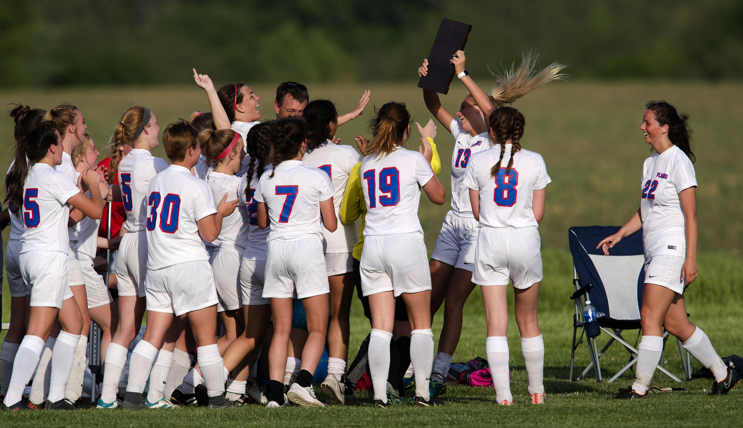 Pleasant Plains' Grace Sinclair and Molly Gebhards deliver the regional hardware to their teammates after defeating Athens during the Class 1A girls soccer regional championship at Pleasant Plains Friday, May 11, 2018. [Ted Schurter/The State Journal-Register]