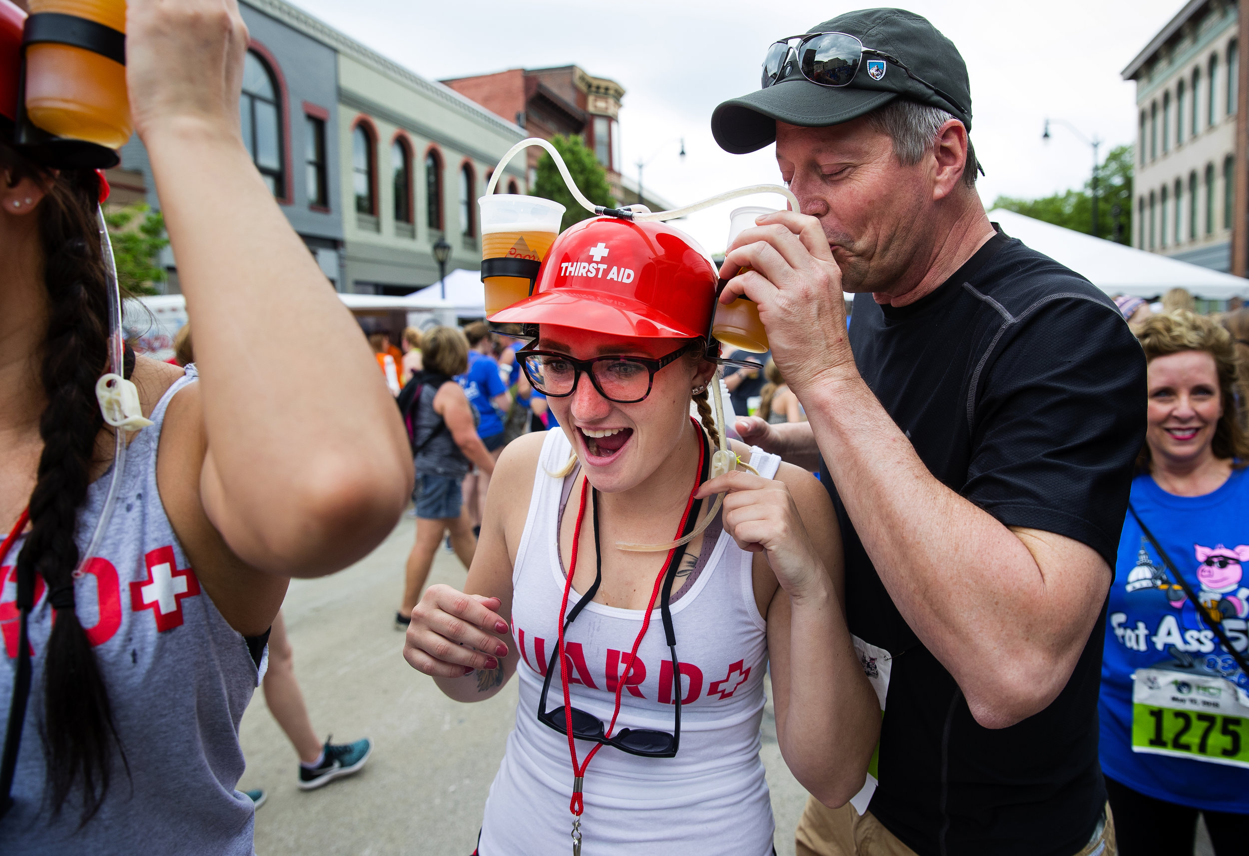 Jeff Wilson helps his daughter Courtney drain a little of of the Blue Moon beer stored in her two-cup hat after they finished the Fat Ass 5K & Street Party for Charity race in downtown Springfield Saturday, May 12, 2018. [Ted Schurter/The State Journal-Register]