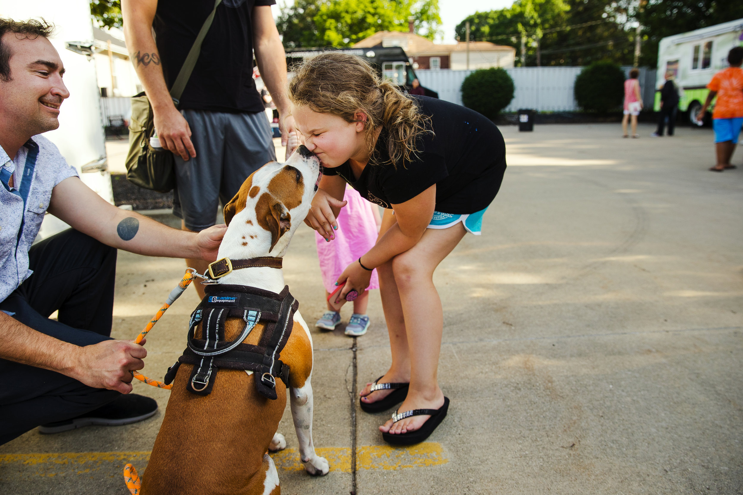 Craig Trudeau holds his dog Pasa as she greets Cadence White with a kiss near the Rolling Meadows Brewery tent at the MacArthur Boulevard Association's Bites on the Boulevard event Tuesday, July 12, 2018. Neighborhood schools are co-hosting the events as a fundraising opportunity for the programs serving the kids of the MacArthur Boulevard surrounding area. Events will continue July 10, August 7, and September 11 from 5:00 p.m. to 9:00 p.m. at 1413 S MacArthur Boulevard. [Ted Schurter/The State Journal-Register]