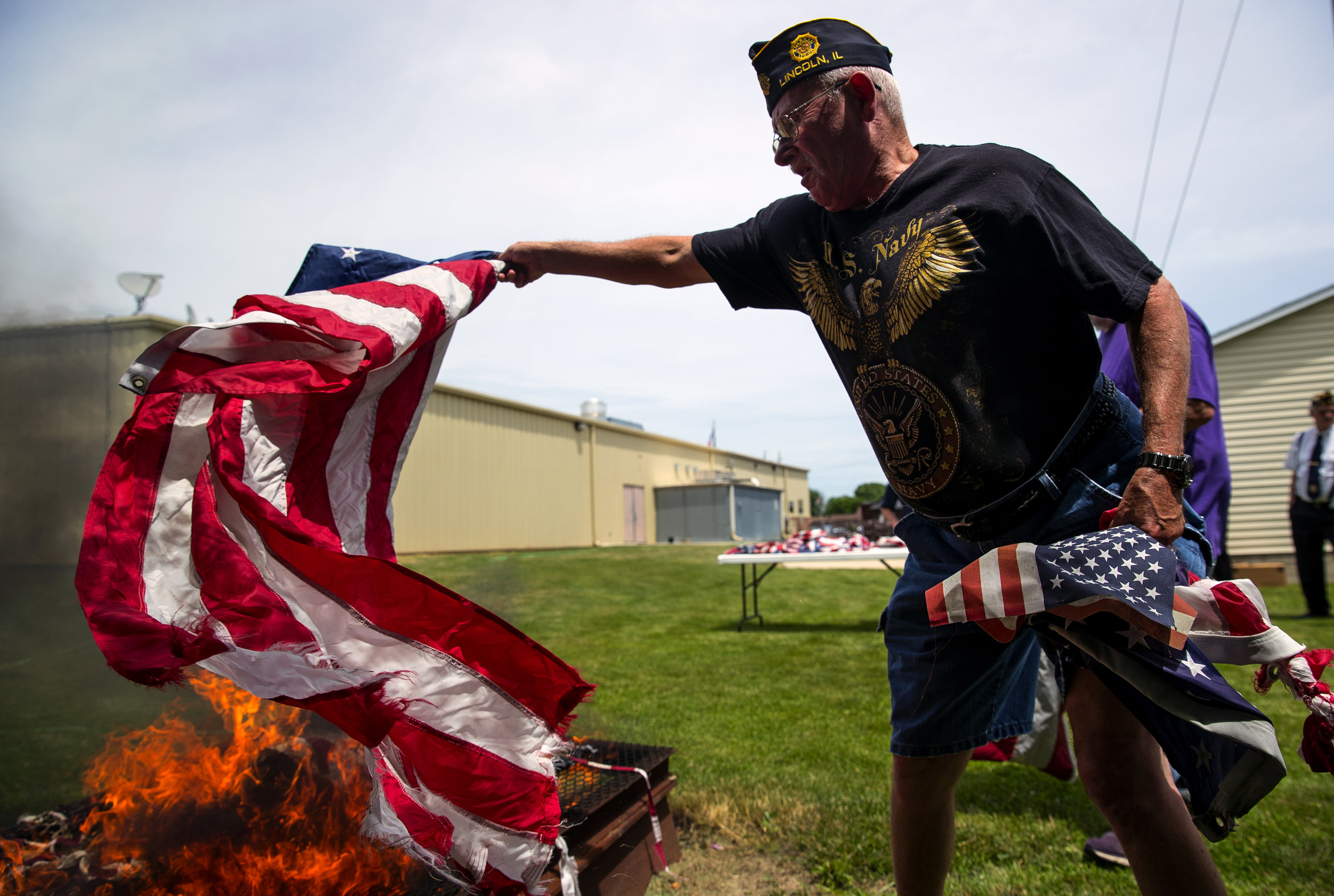 Dave Young adds a U.S. flag to the fire during a flag disposal ceremony hosted by American Legion Post 263 and the Lincoln Chapter of the Daughters of the American Revolution Thursday, June 14, 2018. Thursday was also Flag Day and commemorates the 1777 resolution by the Continental Congress calling for the creation of the United States flag. [Ted Schurter/The State Journal-Register]