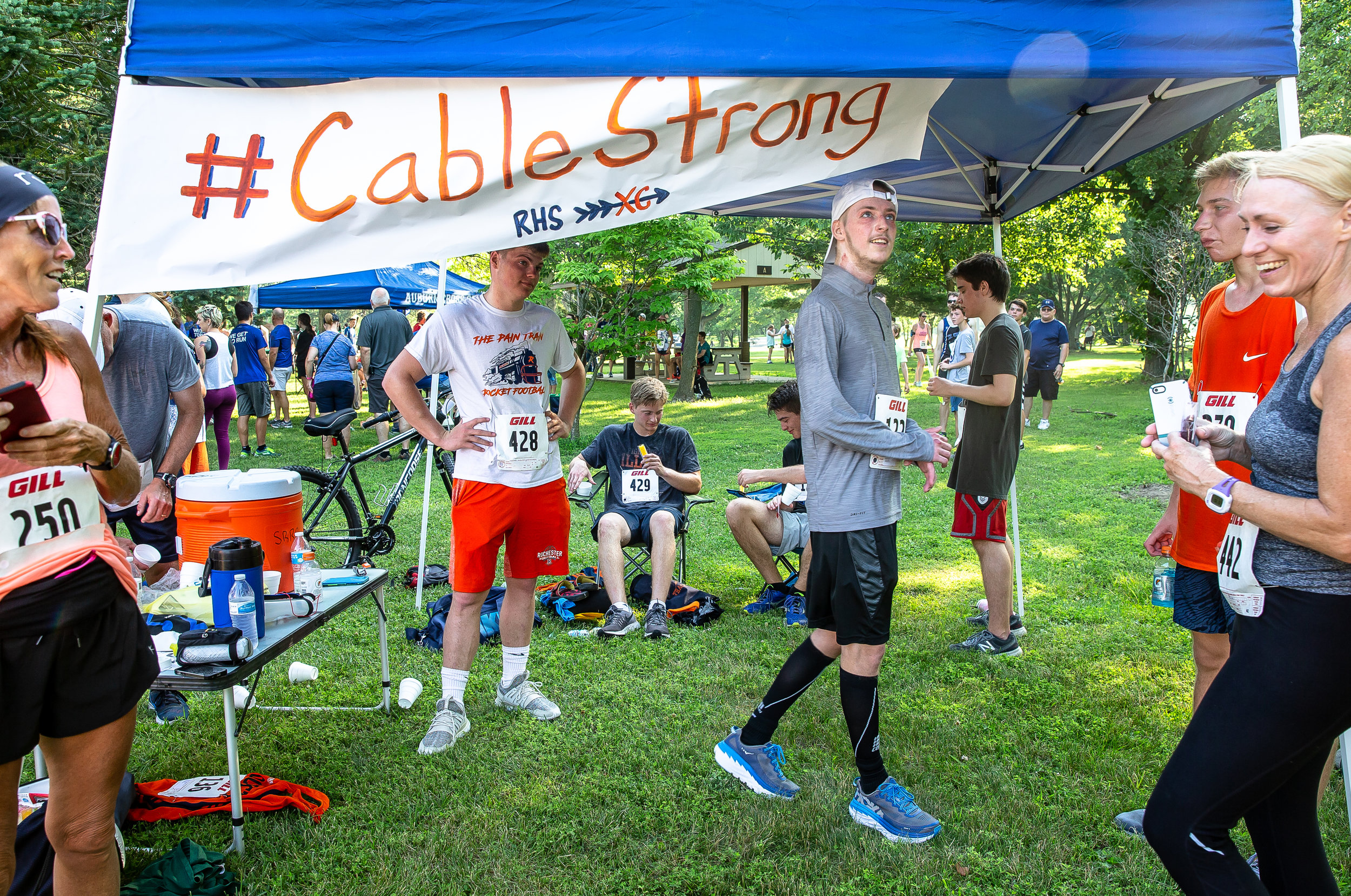 "Rochester graduate Josh Cable, center, walks under the banner of #CableStrong after completing his first race back during the Bob Goldman Memorial Scholastic Challenge 5K at the Center Park, Saturday, June 16, 2018, in Springfield, Ill. Cable suffered major injuries in a house fire on May 1 that he spent 24 days in the hospital recovering from. ""It definitely feels good to be back, it's what I love doing,"" said Cable. ""It's awesome that people are paying attention to my story and my process. It definitely motivates me to do better and be better and hopefully I'm doling the same to them."" [Justin L. Fowler/The State Journal-Register]"