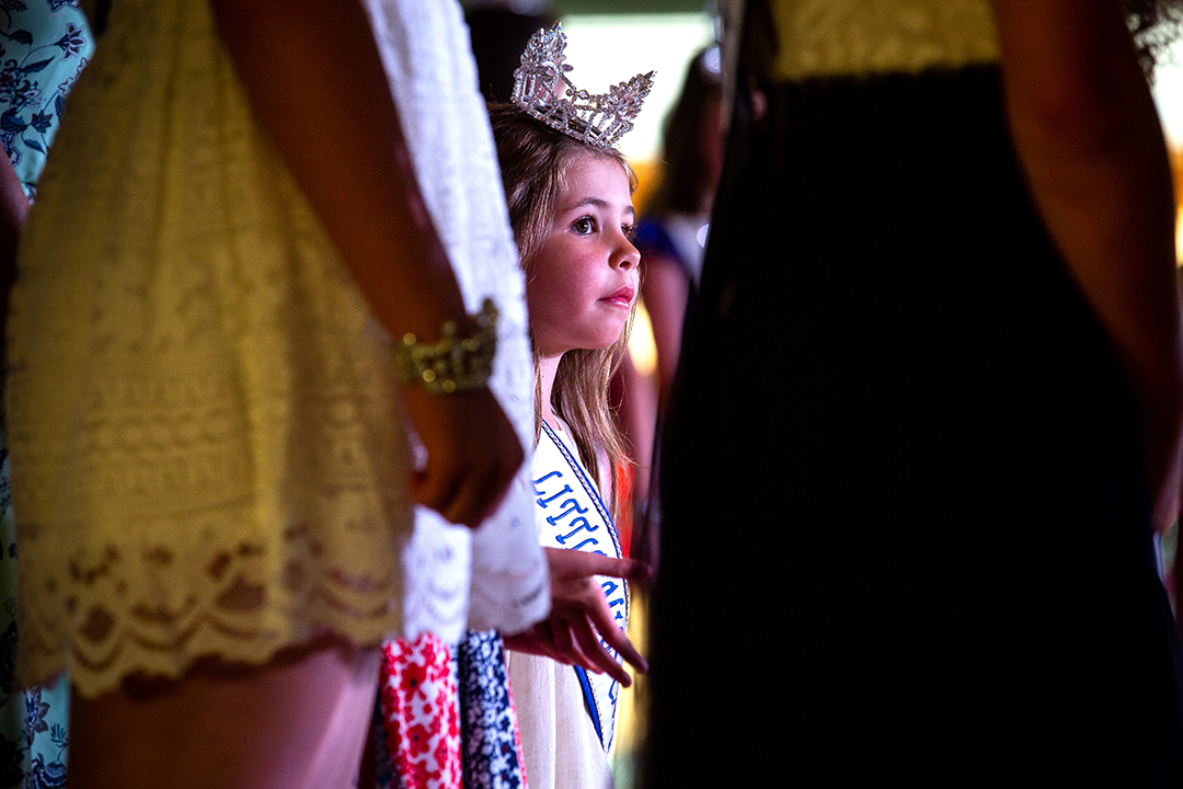 Charlee Steward, the 2018 Little Miss Carlinville, watches other pageant royalty from the area introduce themselves during the Sangamon County Fair Queen pageant Saturday, Tuesday, June 12 at the Sangamon County Fairgrounds in New Berlin, Ill. [Rich Saal/The State Journal-Register]