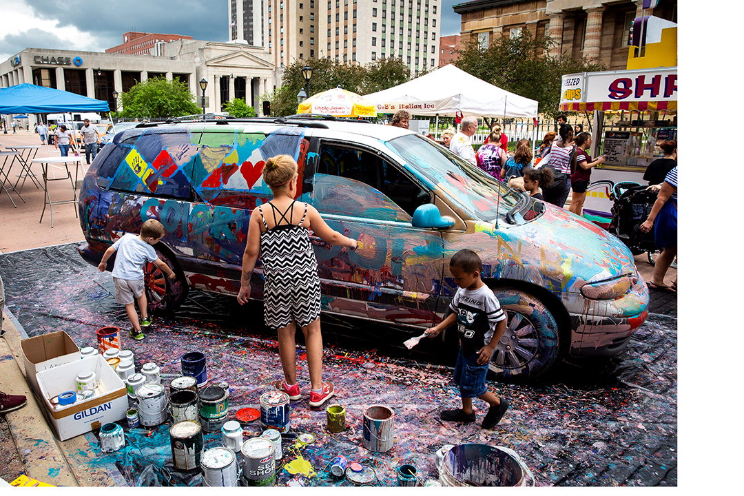 A minivan donated by Green Toyota that had been destined to be crushed, is covered with paint by anyone inspired to add their own touch during the 2018 Paint the Street festival hosted by the Springfield Art Association Saturday, June 23, 2018 on Washington Street in Springfield, Ill. [Rich Saal/The State Journal-Register]