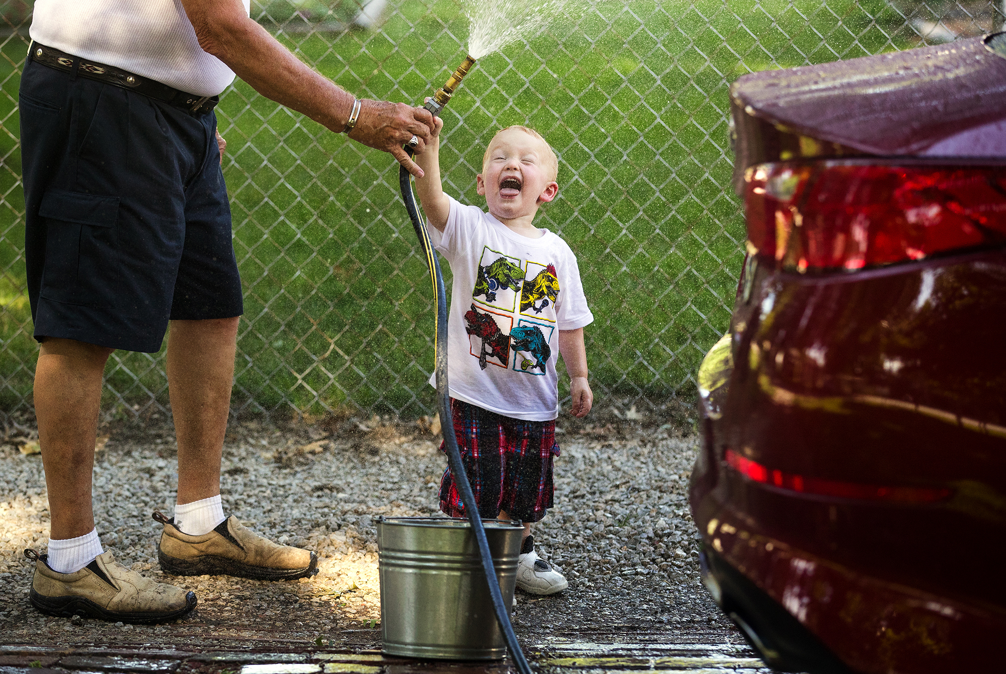 Two-year-old Hayden Leskovisek stands under a spray of his own making as helps his grandfather Gary Leskovisek wash the car in front of their Pawnee home Wednesday, June 20, 2018. According to his grandpa, Hayden, who lives next door, stops by after daycare every day to hang out. [Ted Schurter/The State Journal-Register]