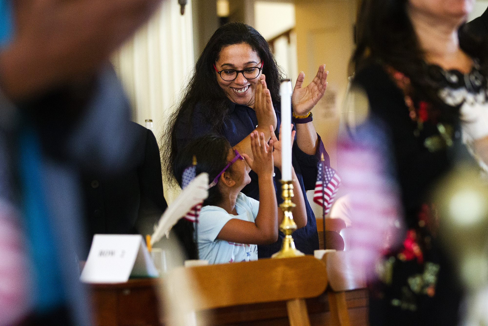 Archana Rajan smiles at her daughter Nakshatra Nambiar as candidates for naturalization applaud after taking their oath during a Naturalization Ceremony at the Old State Capitol Friday, June 22, 2018. [Ted Schurter/The State Journal-Register]