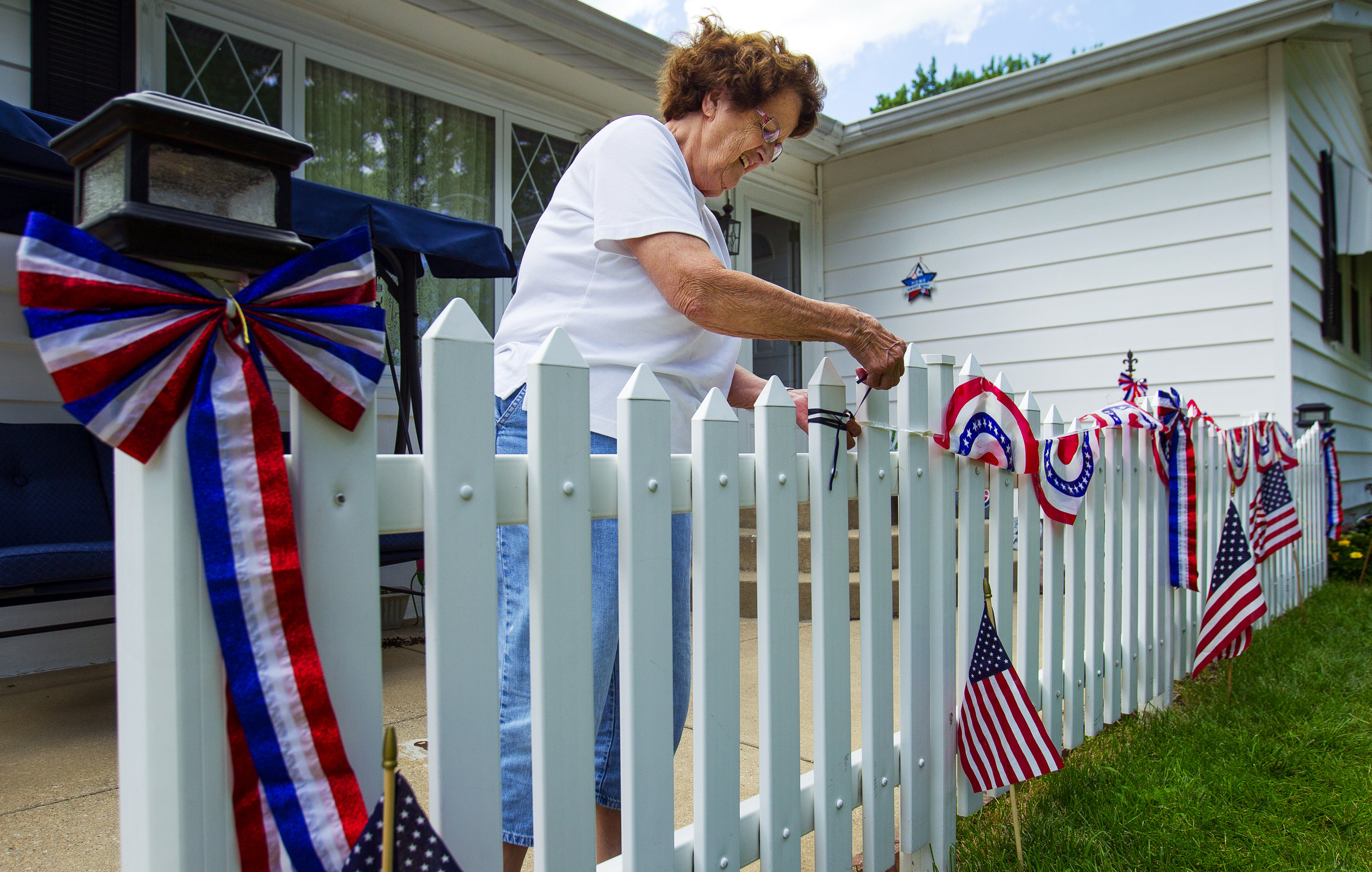 Delores Ball adjusts the patriotic bunting on the fence in front of her Springfield home Monday, July 2, 2018. Ball said the annual display has become a little smaller recently as she has shared her collection with a five-year-old grandson who likes to decorate for the holiday, too. [Ted Schurter/The State Journal-Register]