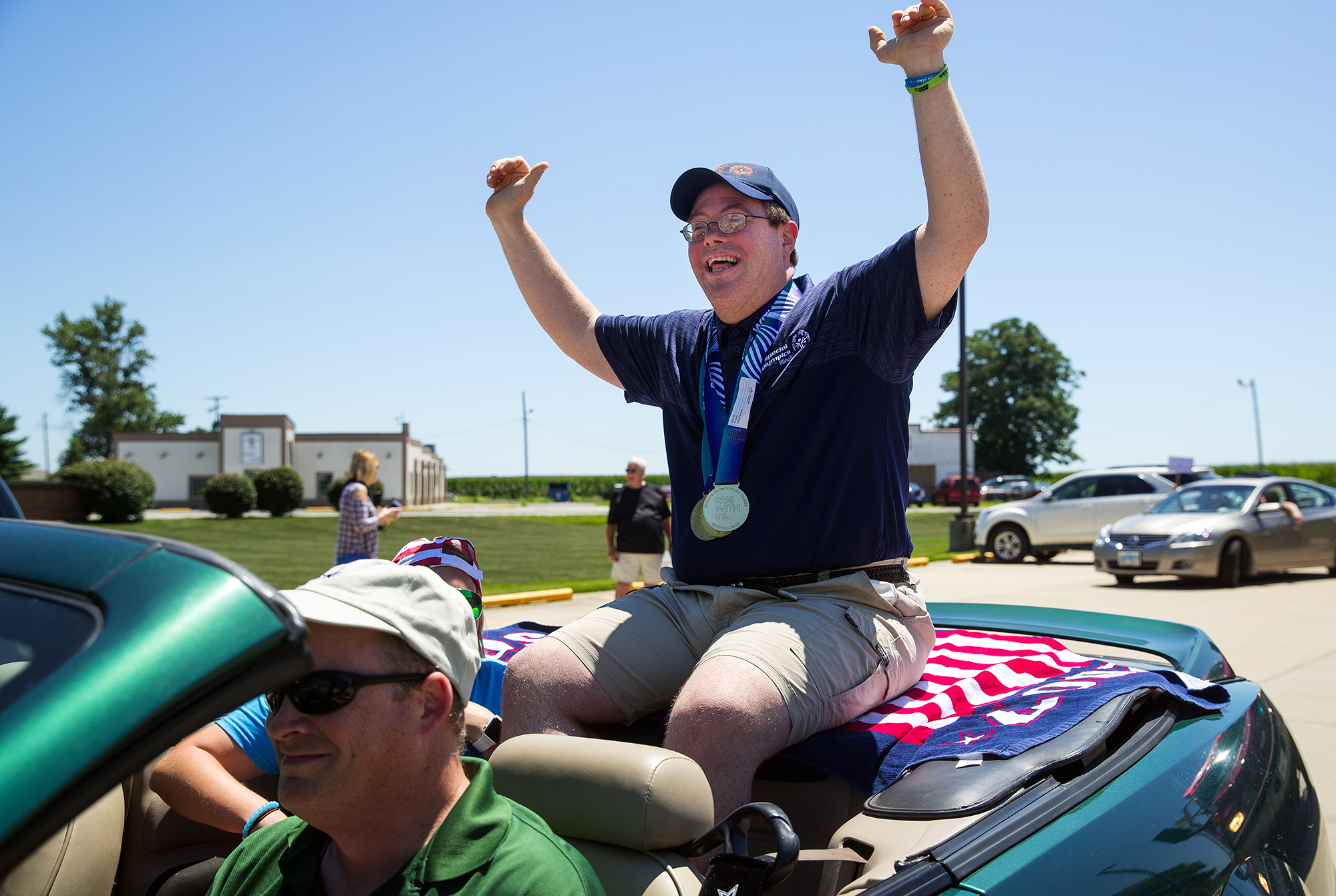 Jonathan Meis waves to the crowd as he departs on a parade in New Berlin in honor of his participation in the Special Olympics Sunday, July 8, 2018. Meis won three medals at the games. [Ted Schurter/The State Journal-Register]