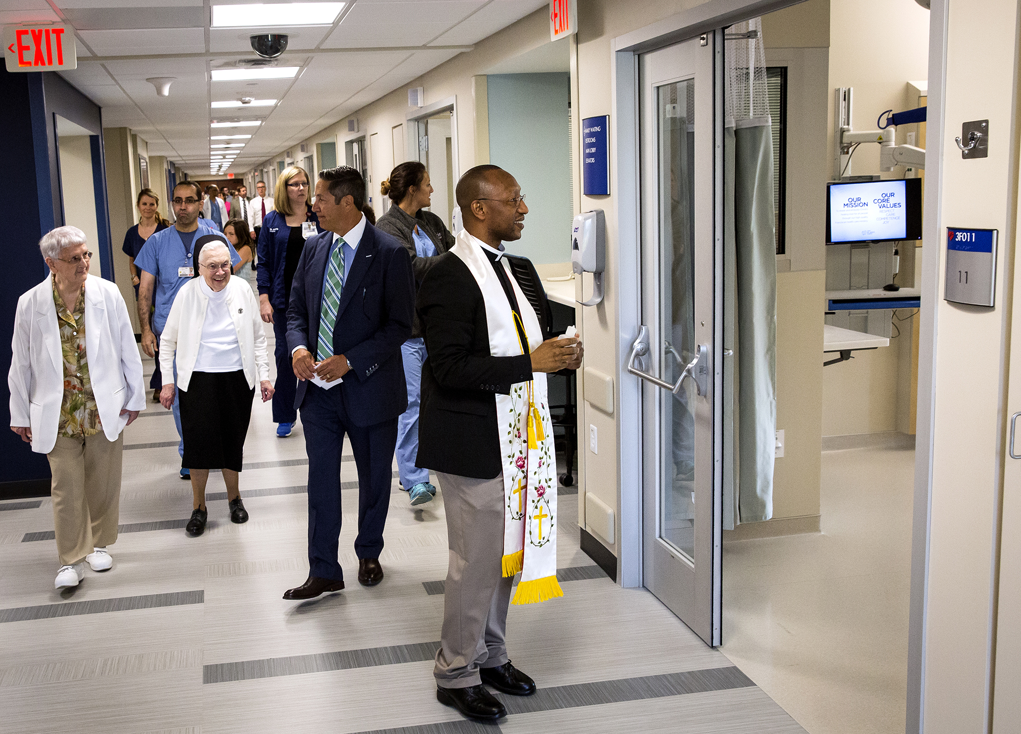 Fr. Fredrick Mbiere, HSHS St. JohnÕs Hospital chaplain, blesses rooms in the hospital's new 14-bed cardiovascular intensive care unit at the Prairie Heart Institute Monday, July 9, 2018 in Springfield, Ill. The $7.9 million project adds larger rooms that include showers, reclining chairs, televisions, storage space for personal belongings and large windows for access to natural light to help with the healing process. The space will be open for patients next Monday. [Rich Saal/The State Journal-Register]