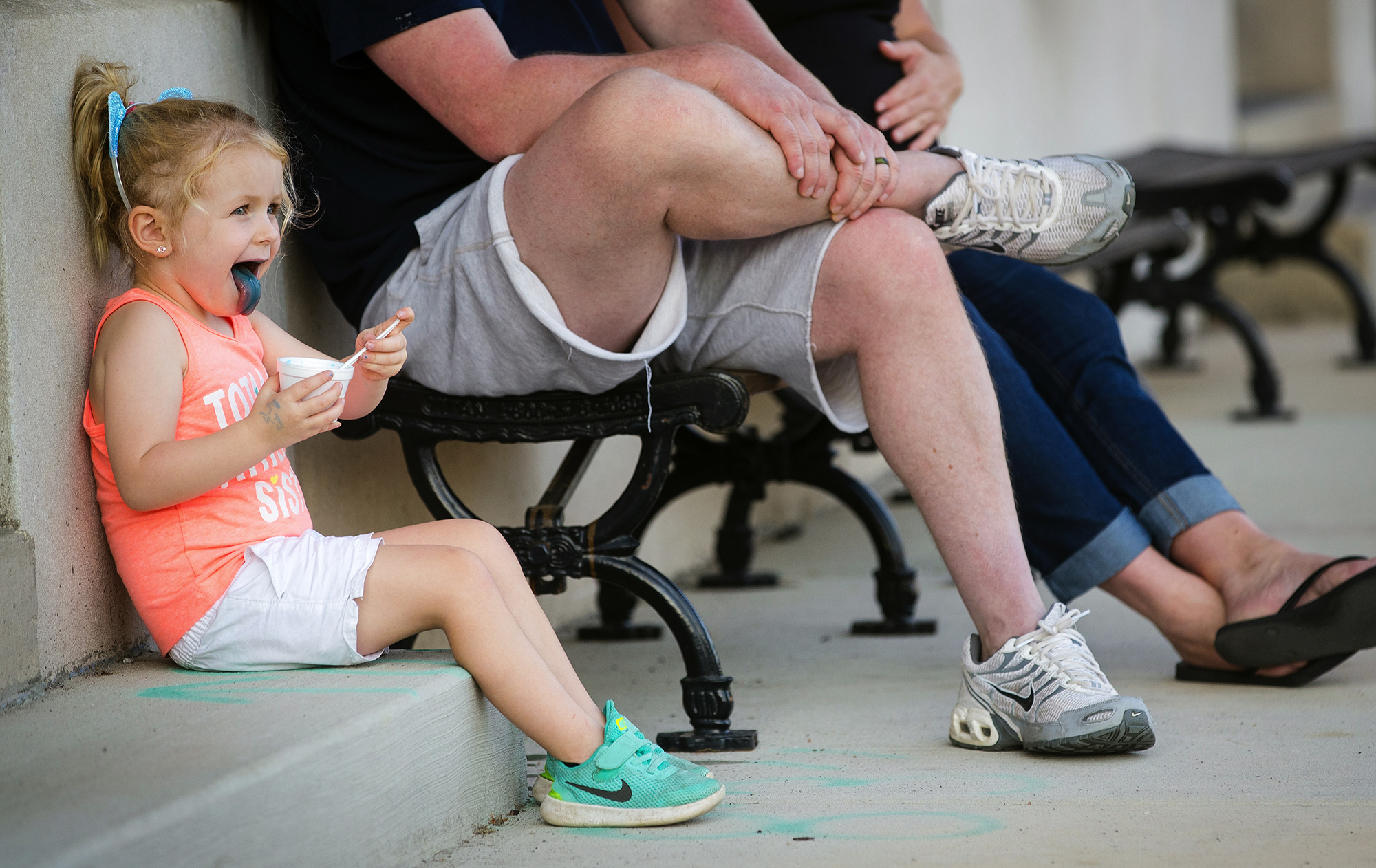 Collyns Constant, three, licks her lower lip with a blue, raspberry flavored tongue as she sits with her parents, Dustin and Ashley Constant, while enjoying an icee in downtown Williamsville Thursday, July 12, 2018. [Ted Schurter/The State Journal-Register]