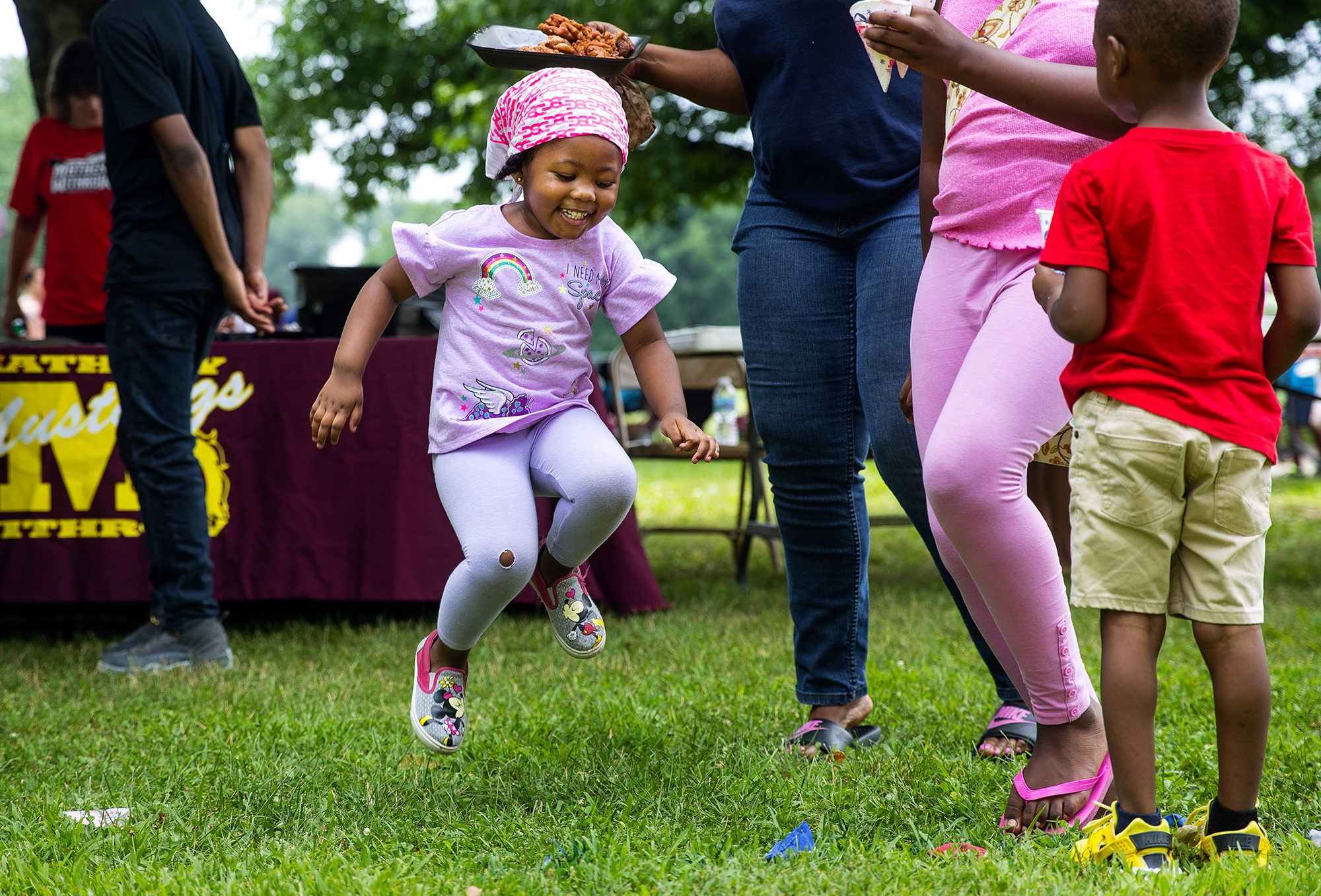 Three-year-old Kemonie Frazier leaps into the air in celebration after tossing a bag through a hole in the bean bag toss during the Back to School Block Party hosted by the Stop the Violence Project at Jaycee Park Saturday, July 14, 2018. [Ted Schurter/The State Journal-Register]