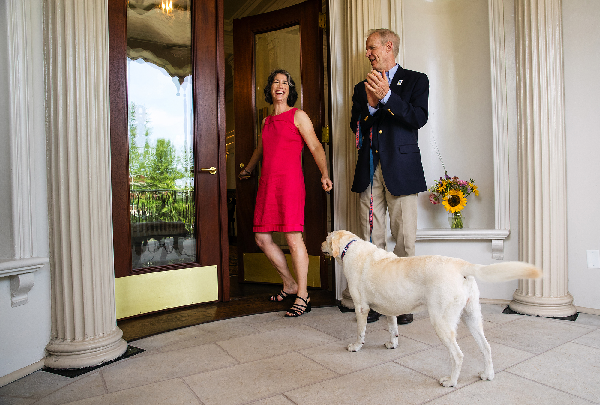 First Lady Diana Rauner opens the door to the Illinois Governor's Mansion with her husband Illinois Gov. Bruce Rauner and their dog Stella during a grand reopening celebration Saturday, July 14, 2018. [Ted Schurter/The State Journal-Register]