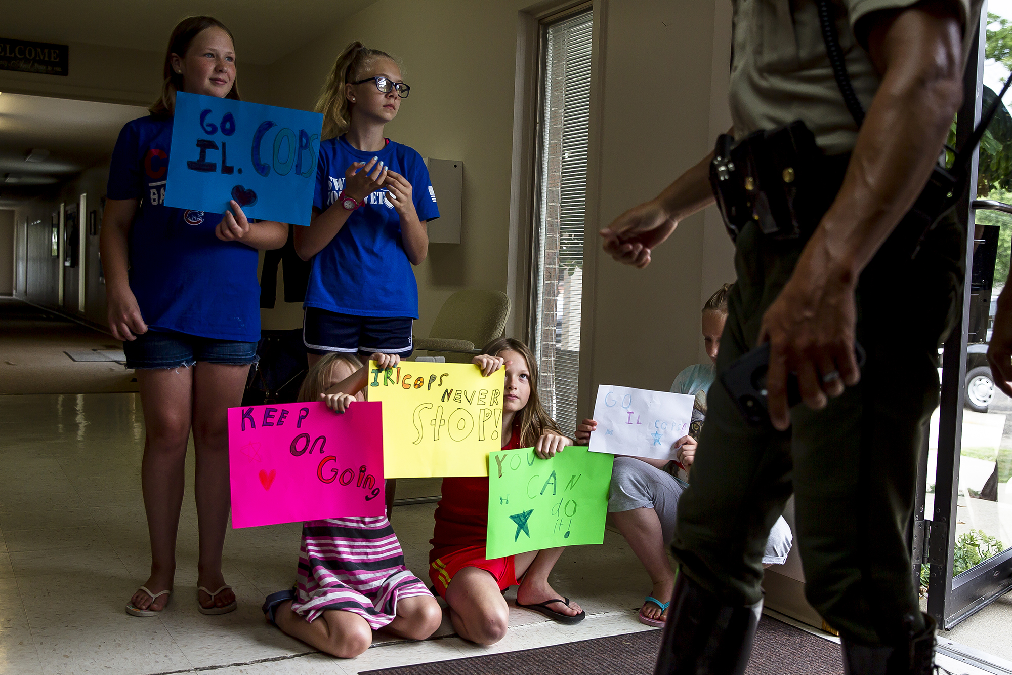 Caroline Kinkade, 9, center, peaks out from behind the signs that she and Savannah Robinette, 11, left, Katy Wiser, 12, Ainsley Robinette, 7, and Annie Robinette, 9, right, made for the cyclists with the Illinois Chapter of Concerns of Police Survivors (ÒC.O.P.SÓ) as they made a stop at the First Baptist Church during the 14th annual Cycle Across Illinois, Thursday, July 19, 2018, in Waverly, Ill. Cycle Across Illinois is a charity bicycle ride to support the Illinois families of law enforcement officers who have died in the line of duty. The ride is over 300 miles and began at the Mississippi River in Alton, Ill., and will end at the Gold Star Families Memorial and Park in Chicago, Ill.[Justin L. Fowler/The State Journal-Register]