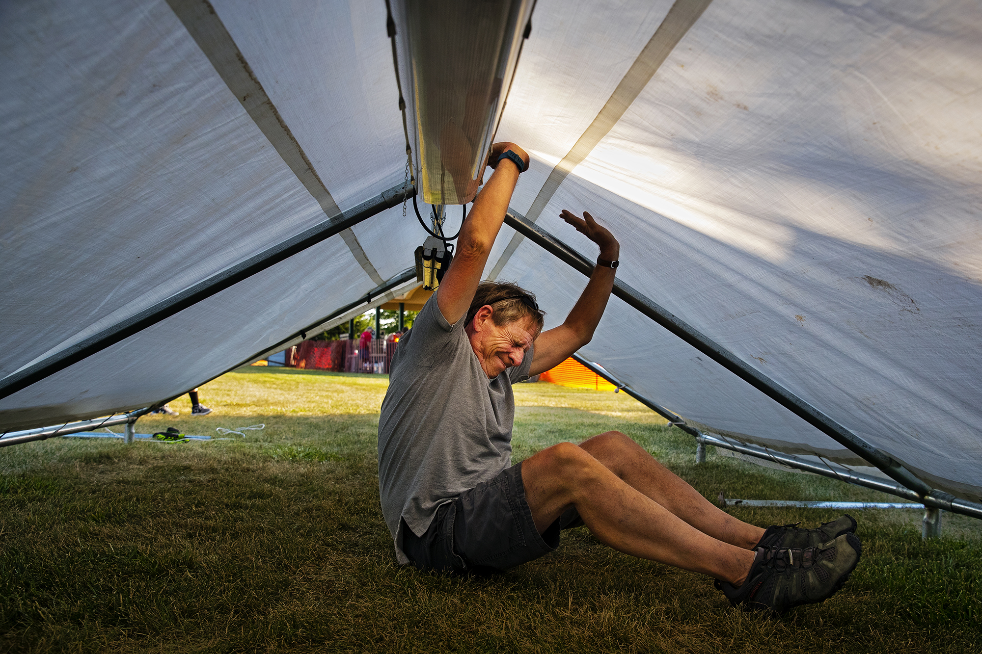 George Perkins strains against the roof of a tent as he helps prepare the Walt Fries booth for the 45th annual Chatham Sweetcorn Festival Thursday, July 19, 2018. The festival kicks off at 5 p.m. with the Sweetcorn Pageant and continues all day Saturday. [Ted Schurter/The State Journal-Register]