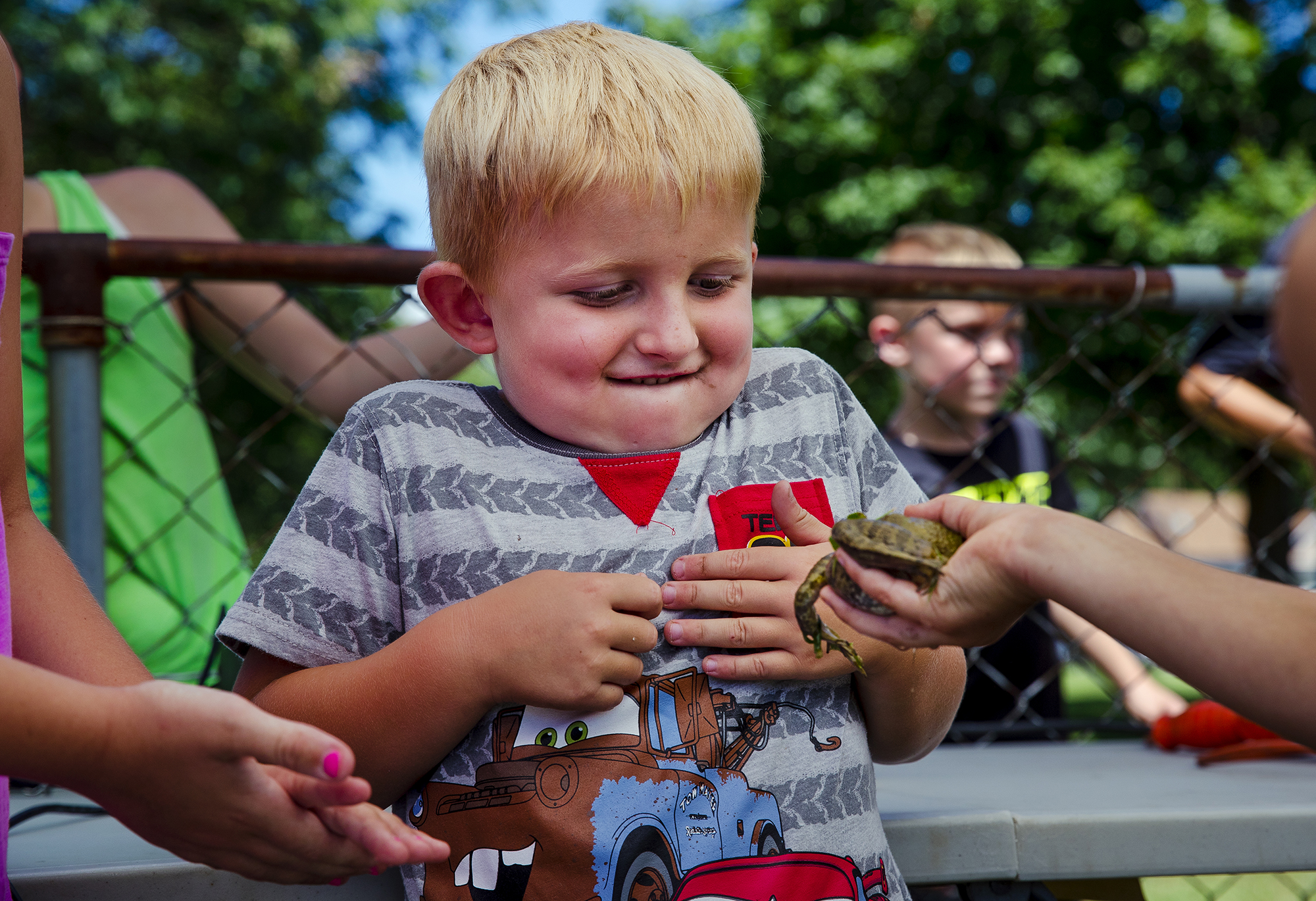 Kaden Rush eyes a bullfrog suspiciously before competing with it during the Frog Jumping Contest at the Morrisonville Homecoming and Picnic Friday, July 20, 2018. Each contestant's frog is given 45 seconds to make 3 jumps and the contestant with the longest cumulative distance receives 40 percent of the entry fees collected. [Ted Schurter/The State Journal-Register]