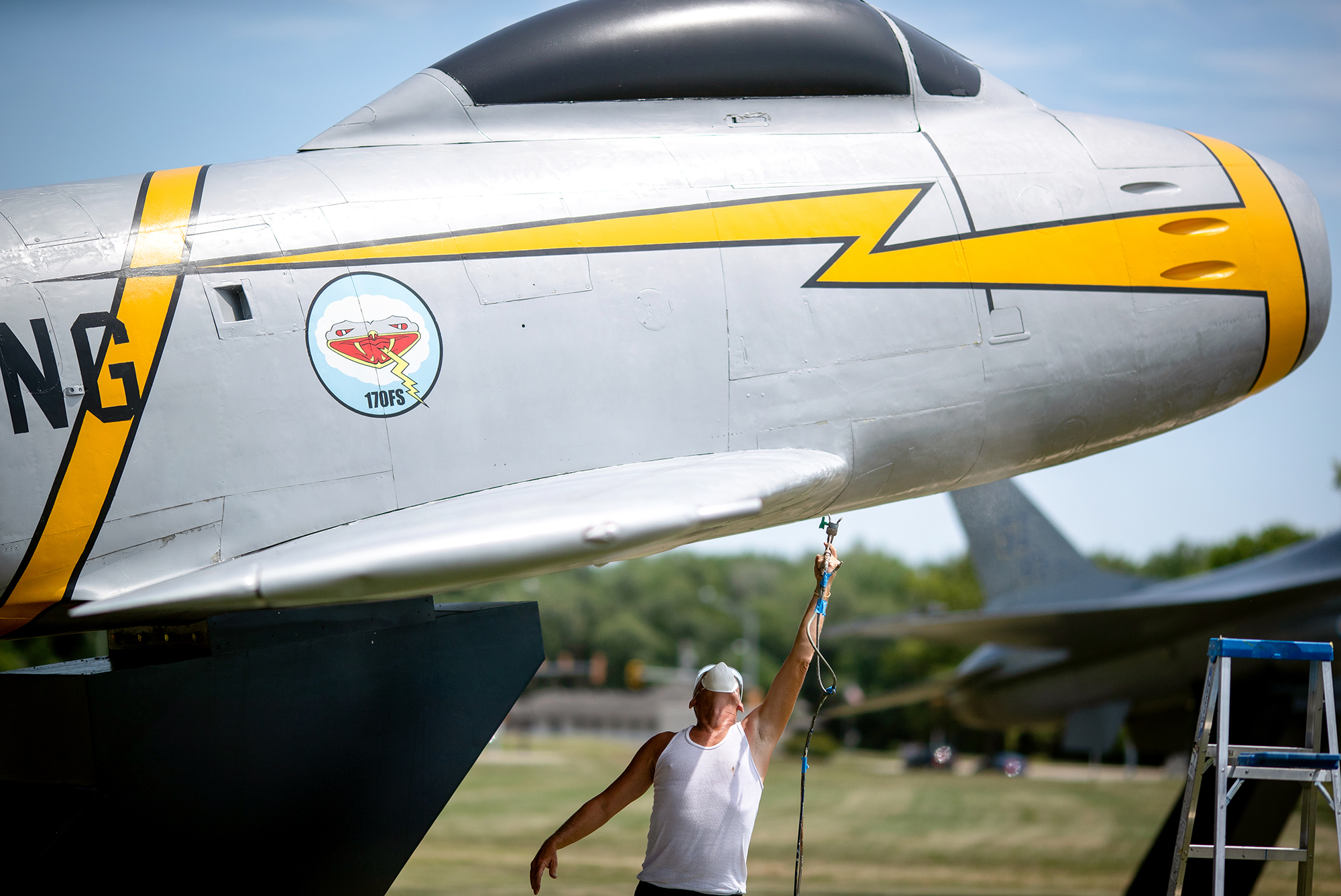 Laurence O'Neal, a painter with Energy Engineering and Controls Military Static Aircraft Painting out of Pennsylvania, applies a new layer of clear coat to the underside of the F86 Sabre on display in Heritage Park outside the Illinois Air National GuardÕs 183rd Wing at the Abraham Lincoln Capital Airport, Wednesday, July 25, 2018, in Springfield, Ill. The painting crew has been working to restore the paint of the planes on display which will take around three weeks to complete. [Justin L. Fowler/The State Journal-Register]