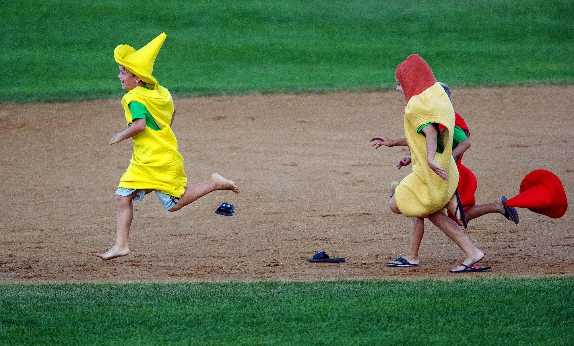 """The """"mustard"""" loses his shoes as the """"ketchup' loses his hat while they sprint around the bases with the hot dog in between innings at Robin Roberts Stadium in Springfield, Ill., Thursday, July 26, 2018. [Ted Schurter/The State Journal-Register]"""