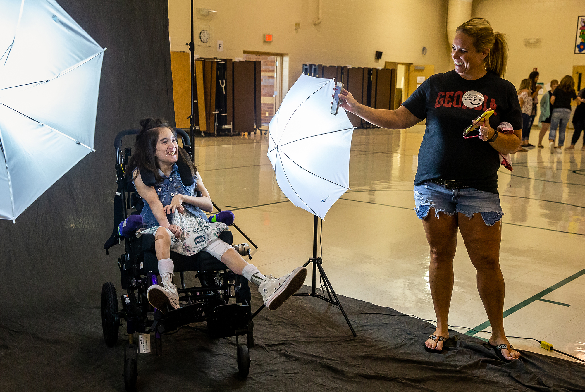 """Morgan Isenburg, 14, erupts in smiles as her mother, Tara Isenburg, right, plays a track from the """"Muppet Babies"""" to get her to smile for a photoshoot during the Changing the Face of Beauty headshot clinic at Lindsay Elementary School, Friday, July 27, 2018, in Springfield, Ill. """"This was great,"""" said Tara Isenburg about the photoshoot experience for her daughter who has cerebral palsy. """"She's never had makeup on her face before."""" Changing the Face of Beauty is nonprofit that aims to empower those living with disabilities through inclusion in advertising and media. [Justin L. Fowler/The State Journal-Register]"""