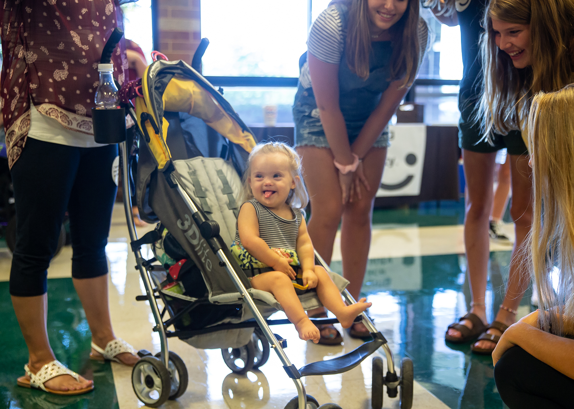 """Eighteen-month-old Emery Pyles, center, lights up with a smile as she showered by attention from the volunteers after her photoshoot during the Changing the Face of Beauty headshot clinic at Lindsay Elementary School, Friday, July 27, 2018, in Springfield, Ill. """"She seems to enjoy it,"""" said Christian Pyles of her daughter Emery who has Down Syndrome. """"She enjoys people and I could see this being something she would enjoy as she gets older if she wants to."""" Changing the Face of Beauty is nonprofit that aims to empower those living with disabilities through inclusion in advertising and media. The headshot clinic provides a collection of digital images for those with disabilities that can be used to submit to casting agencies. [Justin L. Fowler/The State Journal-Register]"""