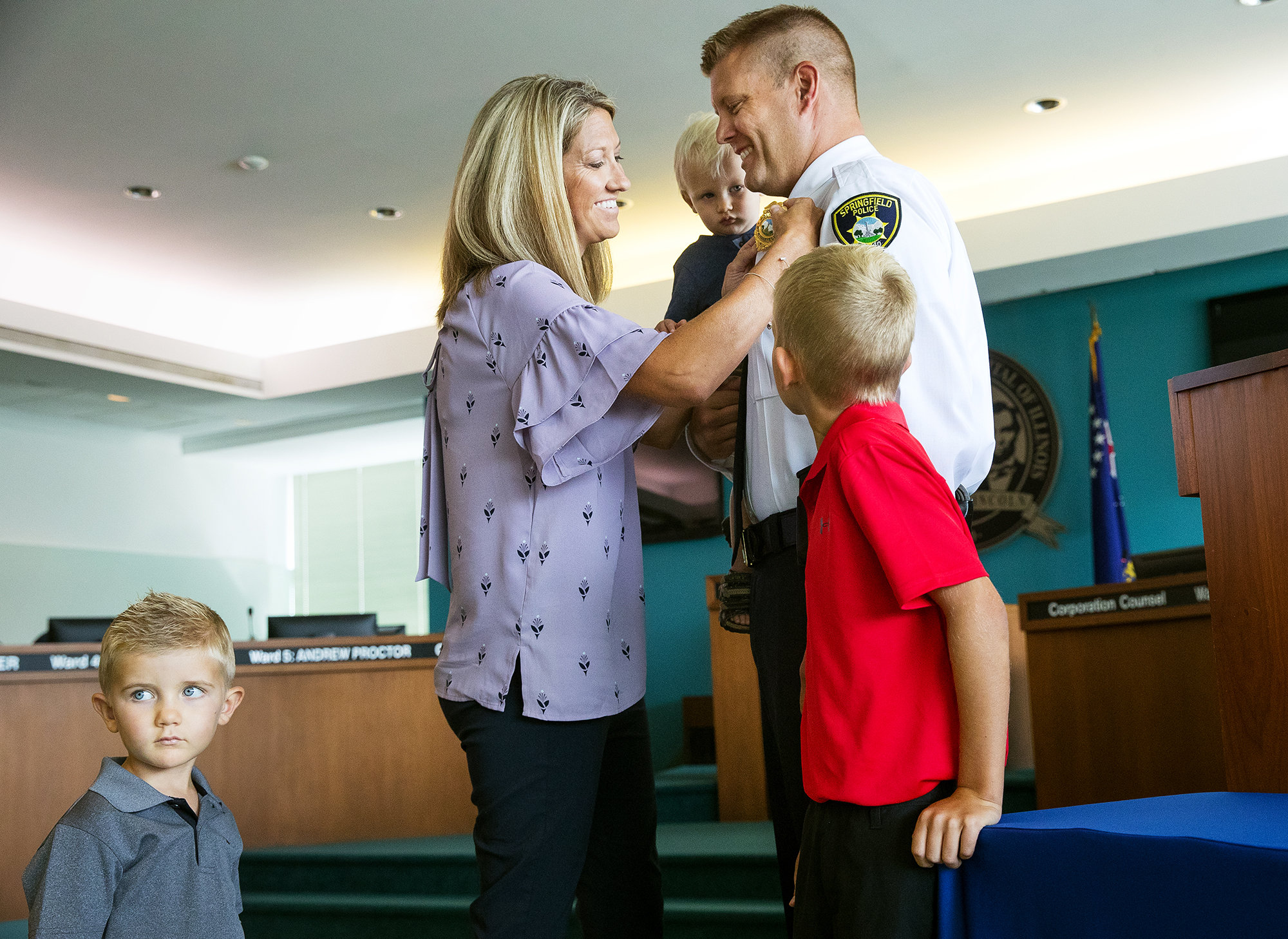 With their three sons, Caden, left, Casey and Jordan, in attendance, Chrissy Stuenkel pins the Commander badge on her husband Joshua during a promotions ceremony in the Springfield City Council chambers Friday, July, 27, 2018. Stephen Dahlkamp was promoted from detective to sergeant and Robert Davidsmeyer was promoted from sergeant to lieutenant.  [Ted Schurter/The State Journal-Register]