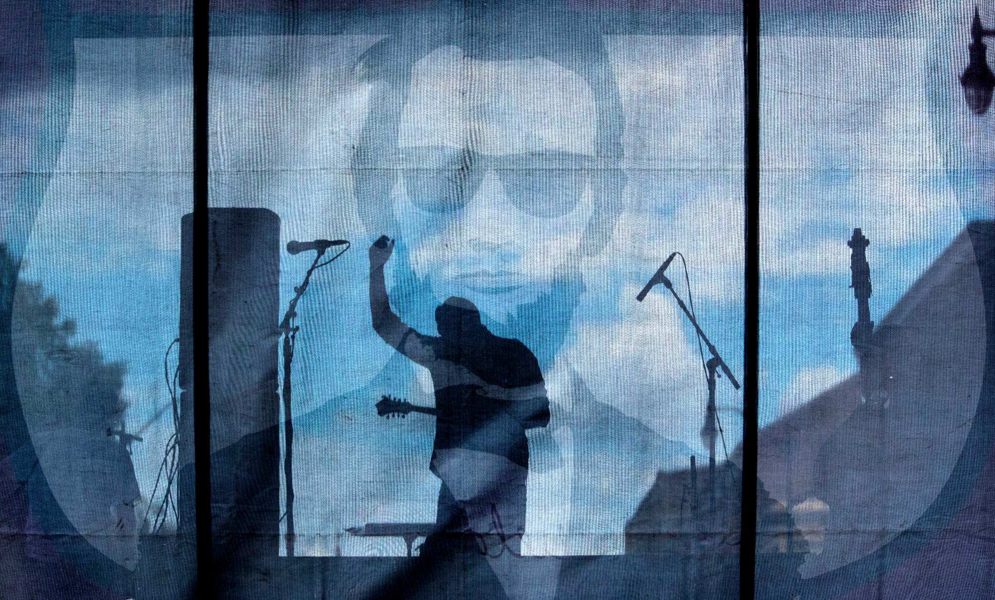 Seen through the stage backdrop of a sunglasses-wearing Abraham Lincoln, Brian Steinhauer performs with Square of the Roots during the Downhome Music Festival Saturday, July 28, 2018. More than two dozen bands performed during the two day event in downtown Springfield. [Ted Schurter/The State Journal-Register]